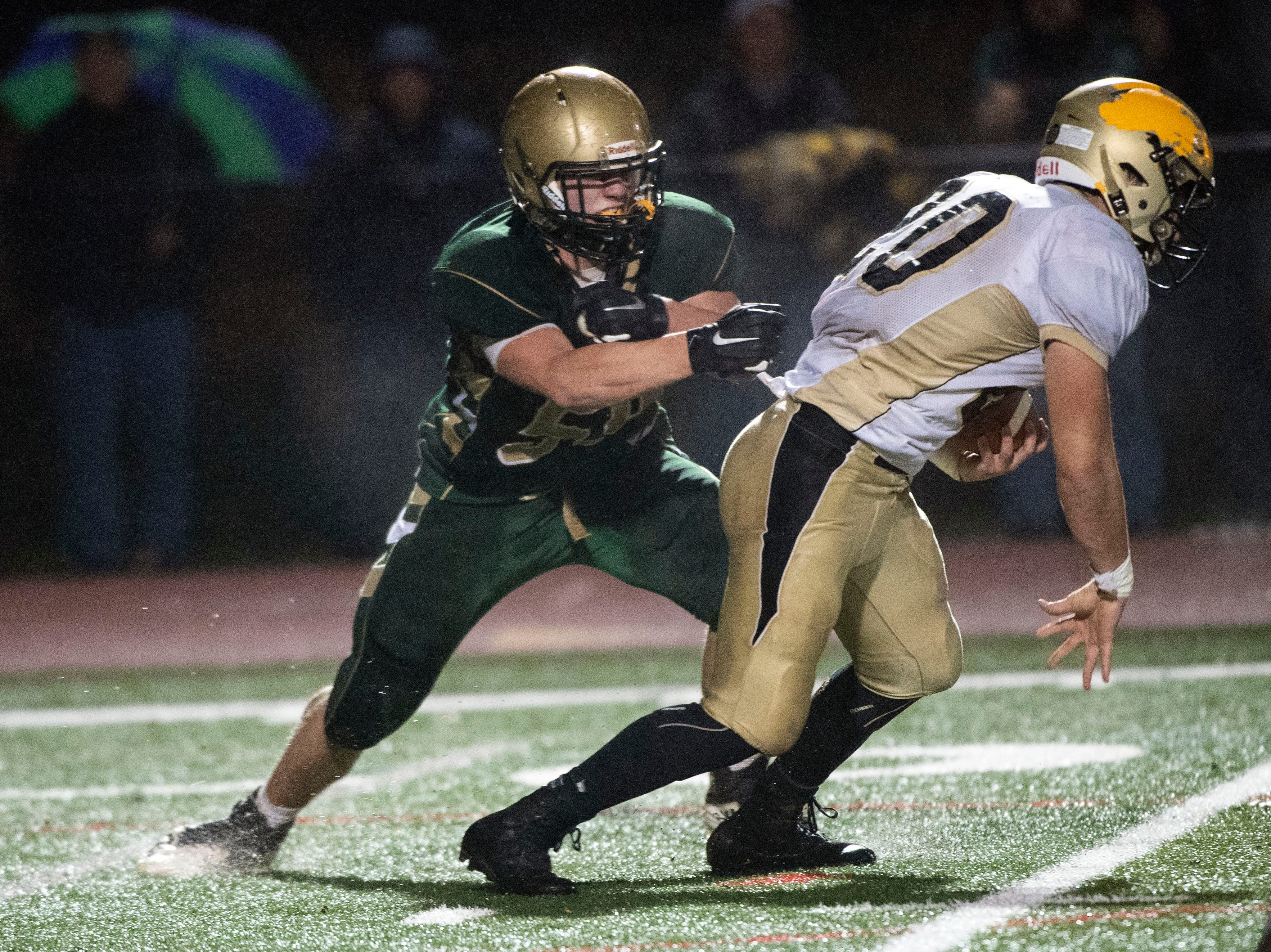 York Catholic's Harris Kohl (59) goes after Delone Catholic's Tyler Monto (20) during the District III 2A championship game at South Western High School on Nov. 9, 2018. The York Catholic Fighting Irish beat the Delone Catholic Squires in overtime, 28-21.