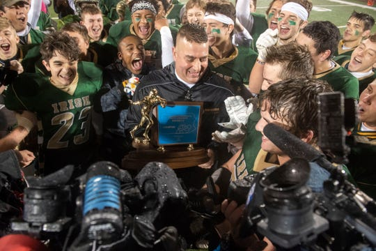 York Catholic surrounds head coach Eric Depew while he talks with media following the Fighting Irish's District III 2A championship at South Western High School on Nov. 9, 2018. The York Catholic Fighting Irish beat the Delone Catholic Squires in overtime, 28-21.