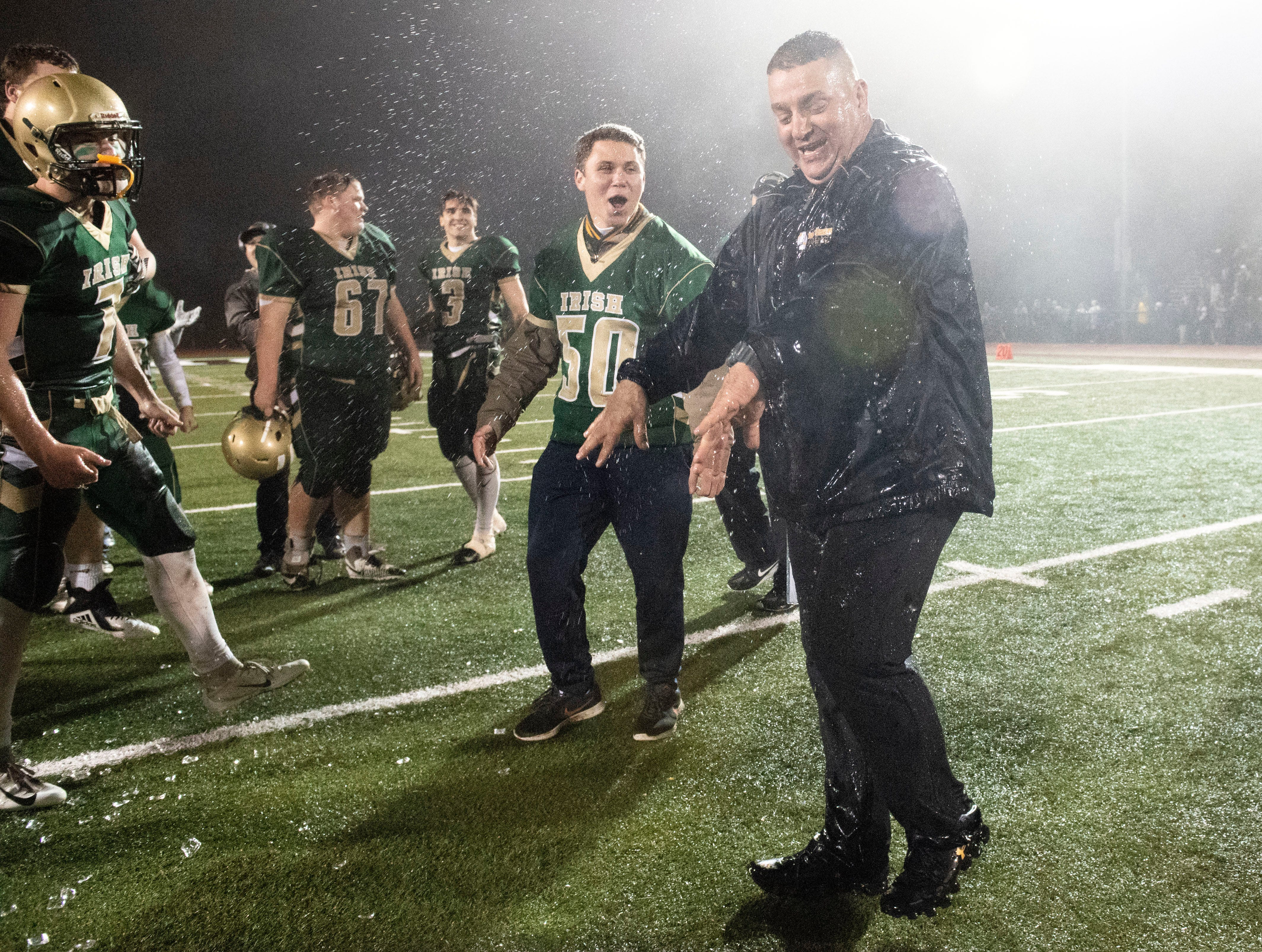 York Catholic head coach Eric Depew shakes water off him after being drenched by a water cooler following the Fighting Irish's District III 2A championship win at South Western High School on Nov. 9, 2018. The York Catholic Fighting Irish beat the Delone Catholic Squires in overtime, 28-21.