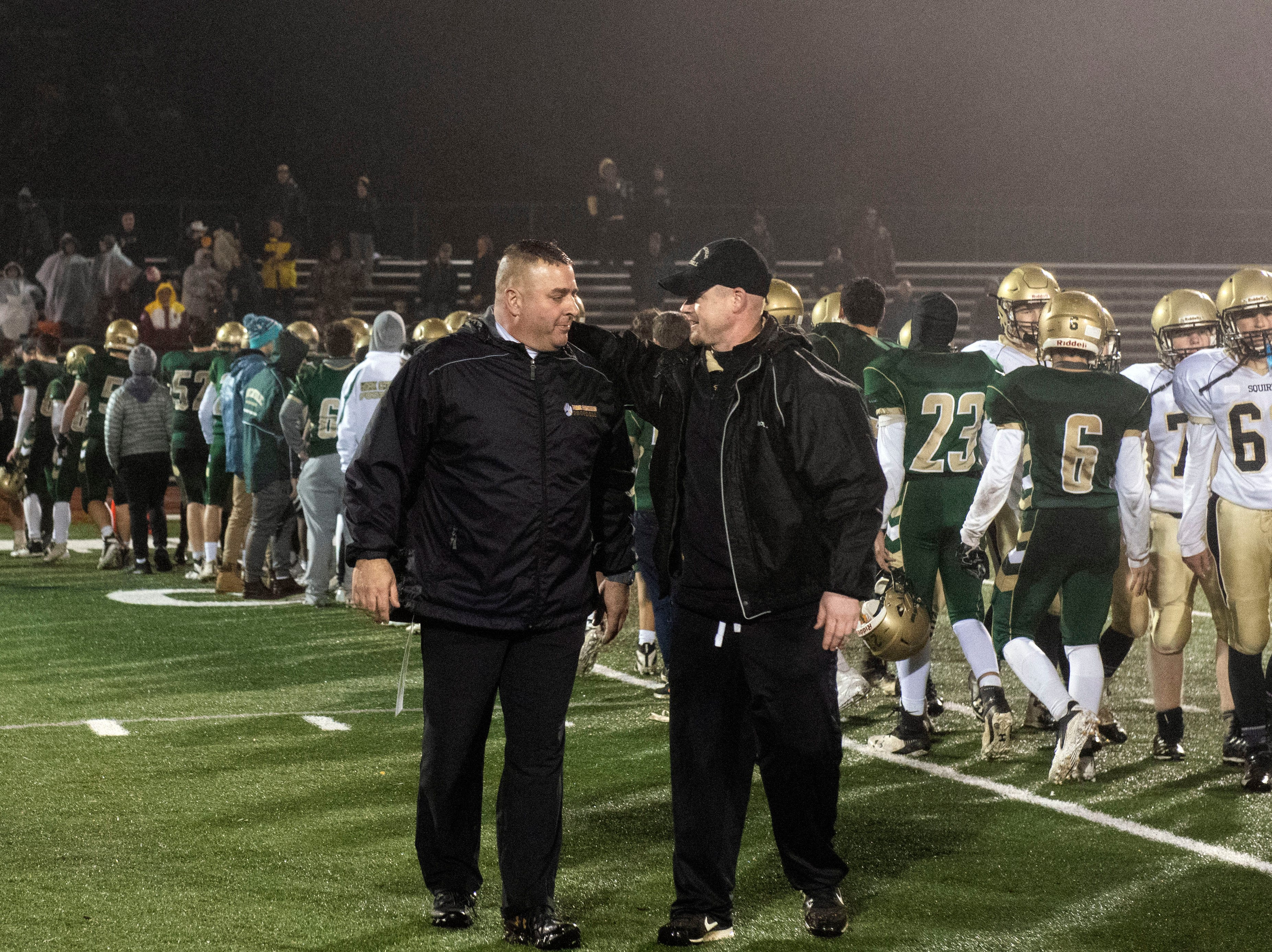 Delone Catholic head coach Corey Zortman, right, congratulates York Catholic head coach Eric Depew after the Fighting Irish won the District III 2A championship at South Western High School on Nov. 9, 2018. The York Catholic Fighting Irish beat the Delone Catholic Squires in overtime, 28-21.