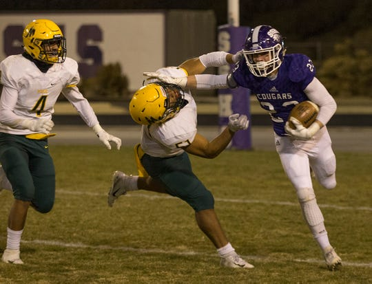 Spanish Springs Parker Luthy (23) straight-arms  Manogue's Kruz Conway (51) on Friday at Spanish Springs.