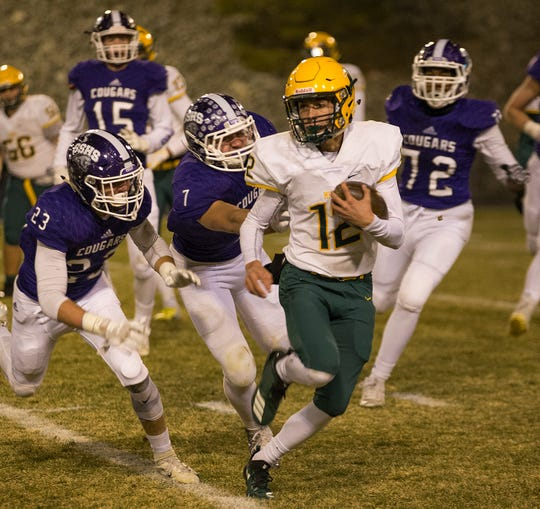 Manogue quarterback Drew Scolari (12) runs away from the Spanish Springs defense on Friday at Spanish Springs.