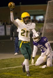 Manogue's Dontell Jackson (21) celebrates after make an interception in the end zone on Friday at Spanish Springs.