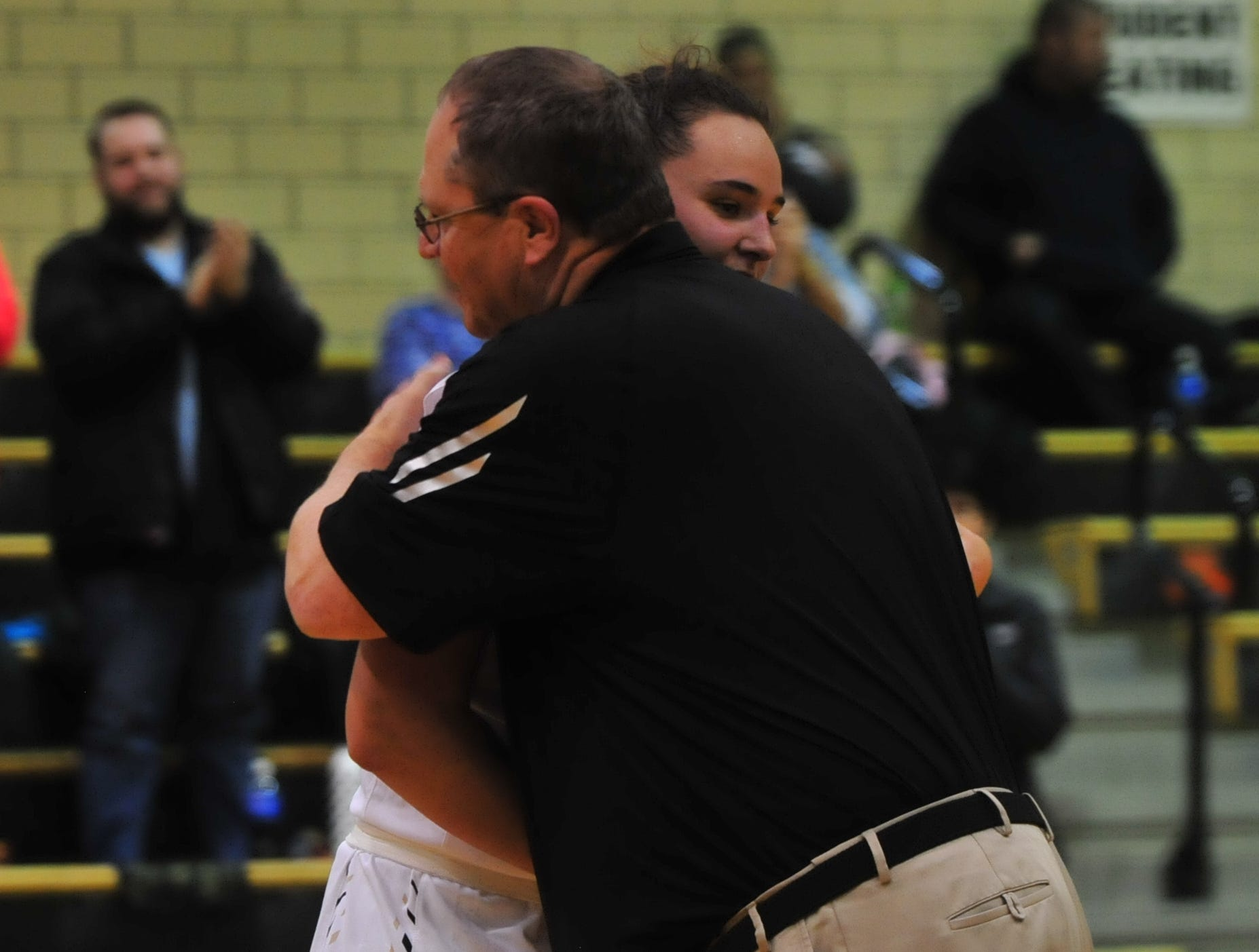 Maddie Lawrence (2) hugs assistant coach Jim Hollinger during an 84-44 girls basketball win over Knightstown Friday, Nov. 9, 2018 at Winchester Fieldhouse.
