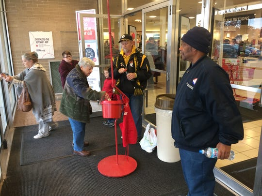 A shopper puts money in the Salvation Army red kettle at JC Penney as Billy Cook and Bracy Ledford Jr. switch bell-ringing shifts.