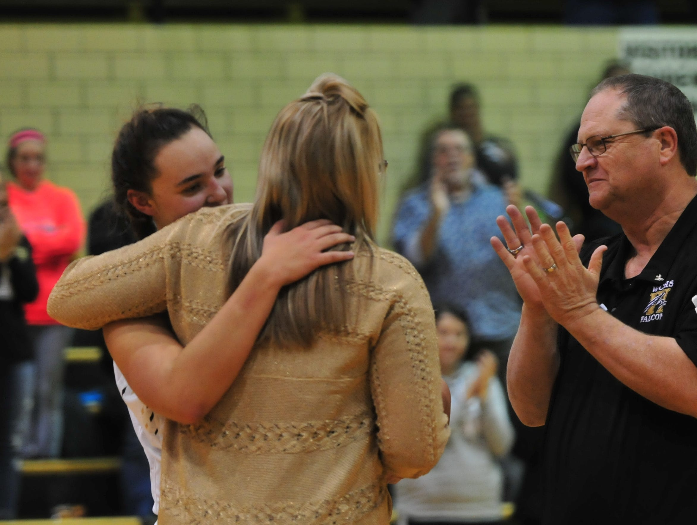 Winchester's Maddie Lawrence, left, hugs head coach Holly Gutierrez, while assistant coach Jim Hollinger applauds during an 84-44 girls basketball win over Knightstown Friday, Nov. 9, 2018 at Winchester Fieldhouse.