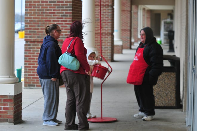 Katherine Mihalus, 5, puts money in a Salvation Army red kettle manned by Howard Potts outside Hobby Lobby. Mihalus was shopping with her grandma Sally James (left) and her mom, Tabitha Mihalus.