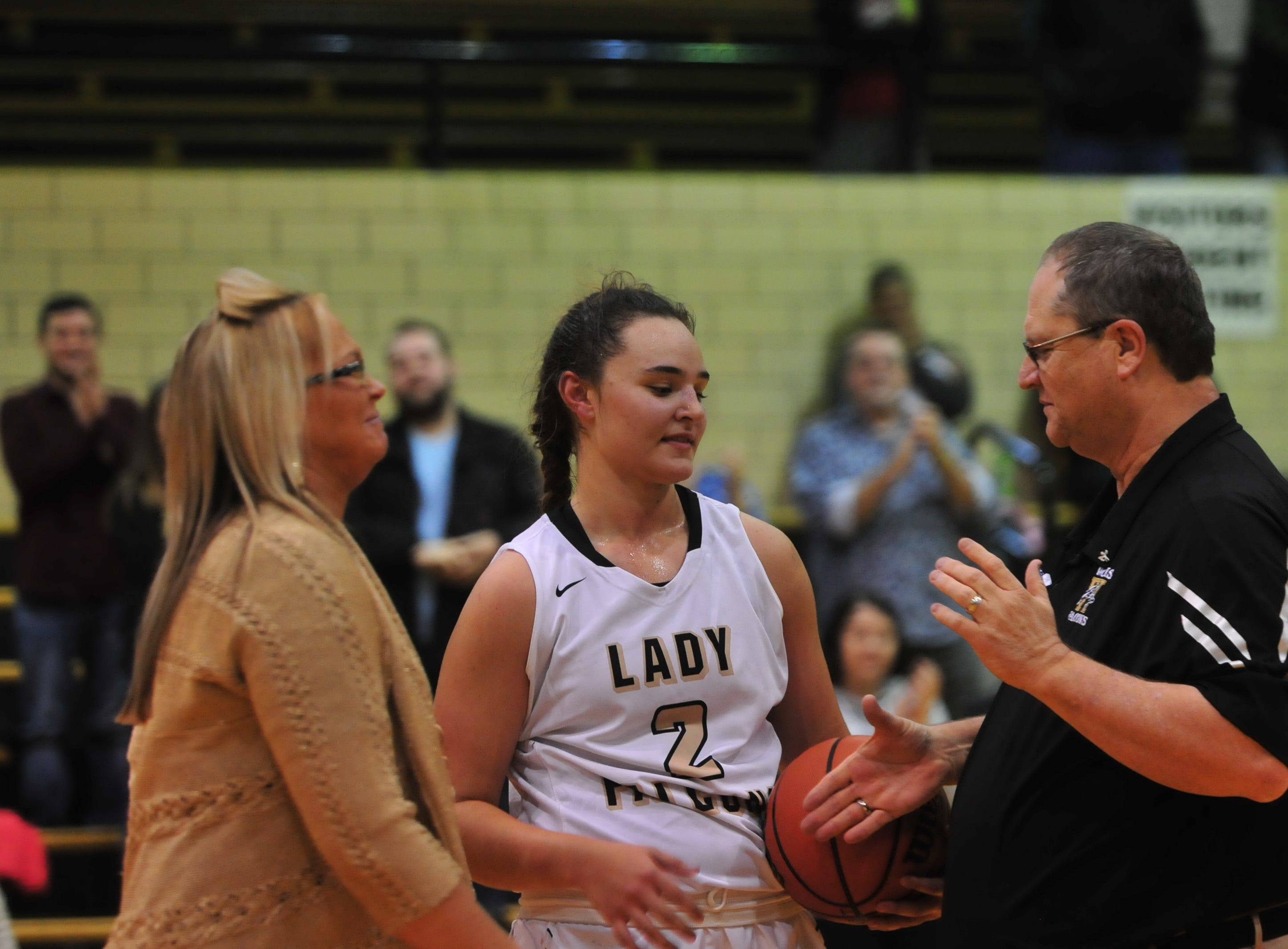 Winchester's Maddie Lawrence (2) shakes hands with assistant coach Jim Hollinger, right, as head coach Holly Gutierrez smiles. Lawrence was honored for scoring her 1,000th career point during halftime of an 84-44 girls basketball win over Knightstown Friday, Nov. 9, 2018 at Winchester Fieldhouse.