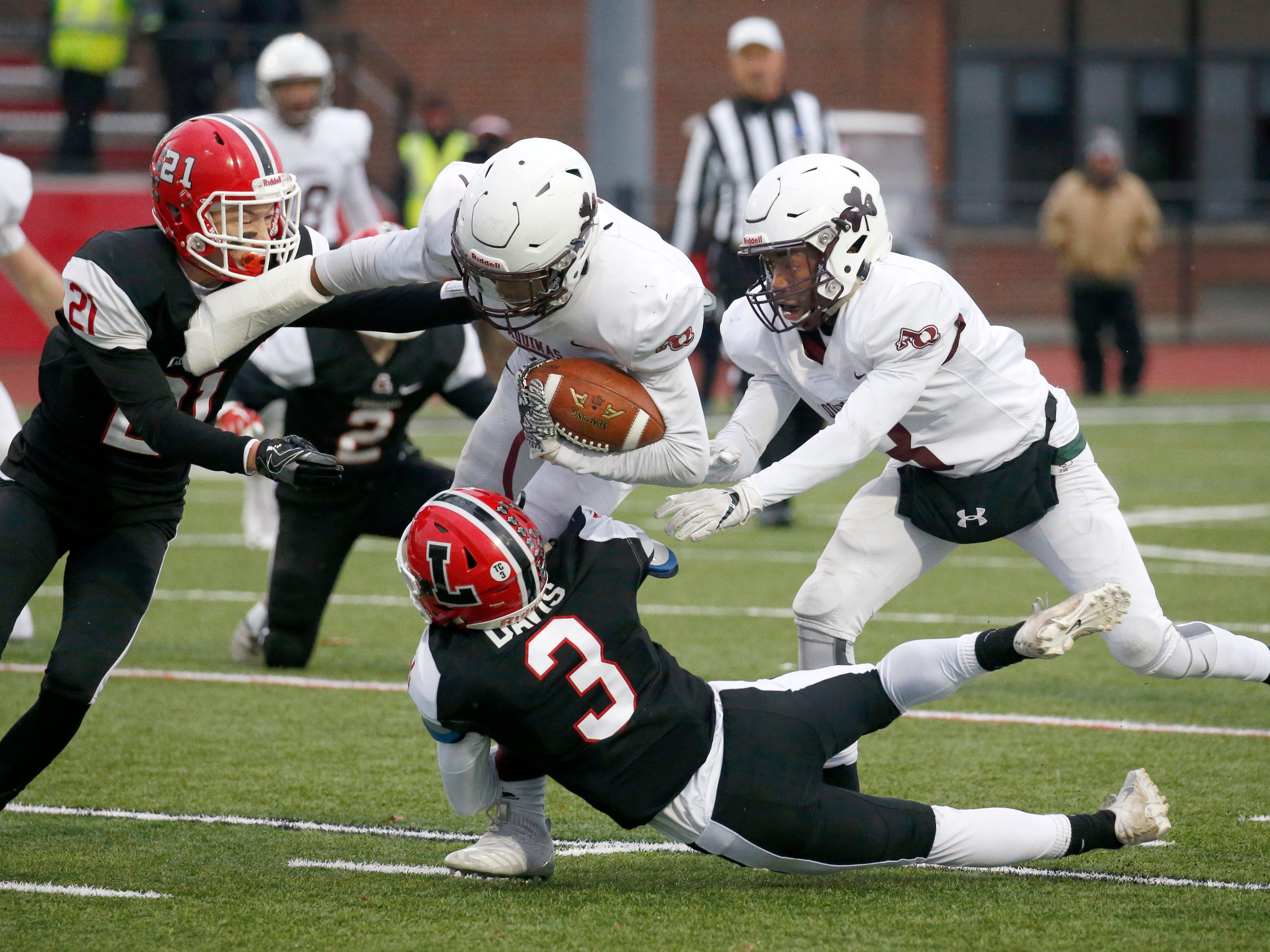 Aquinas' Caron Robinson is tackled by Lancaster's Shawn Davis in the first quarter at Clarence High School on Nov. 10, 2018.