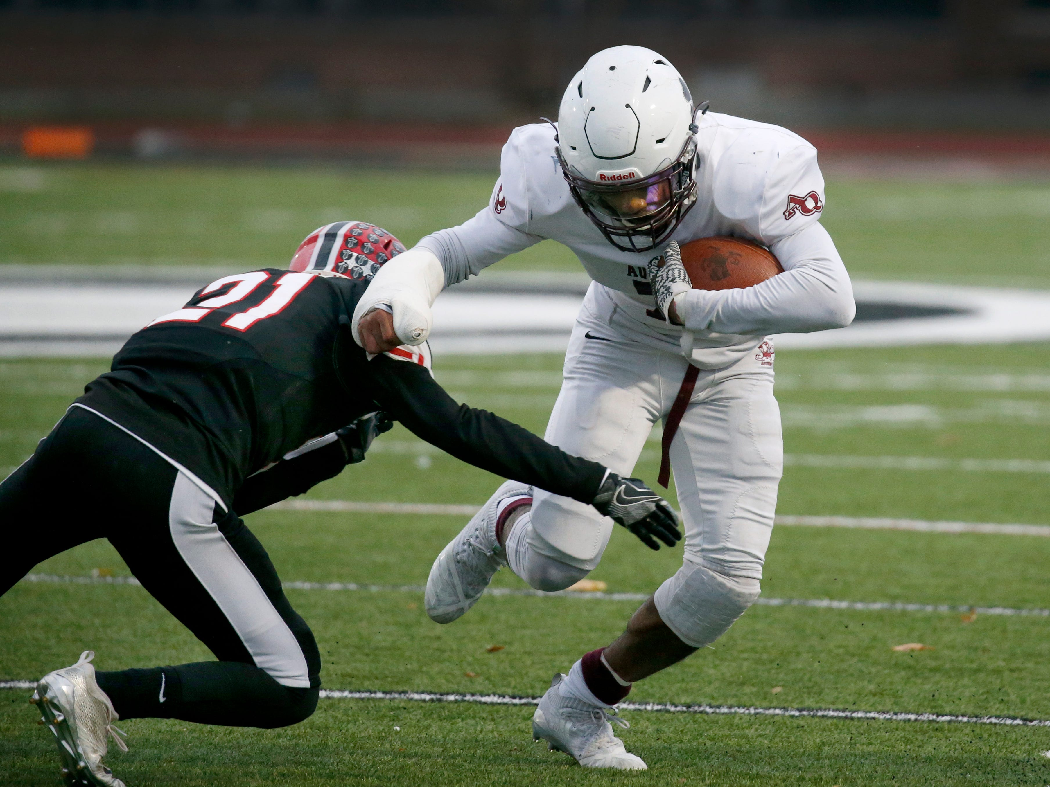 Aquinas' Caron Robinson  is tackled by Lancaster's Nick Meara in the first quarter at Clarence High School on Nov. 10, 2018.