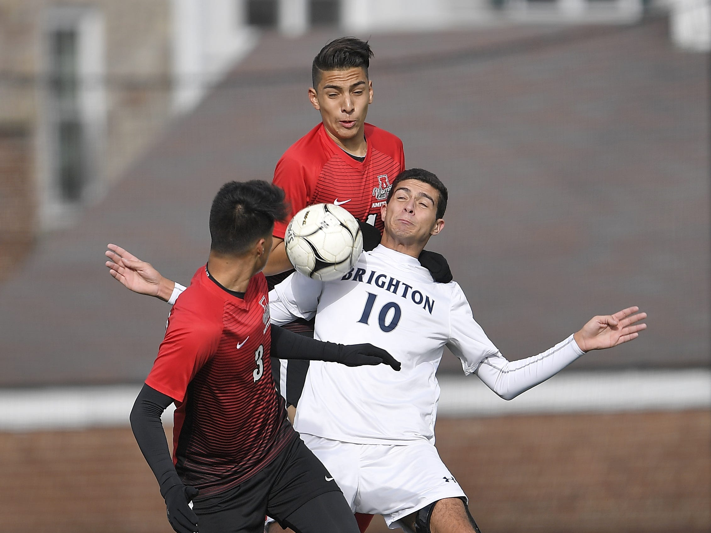 Brighton's Caio De Medeiros (10) tries to control the ball between Amityville's Carlos Ponce, top, and Angel Zavala during a Class A semifinal at the NYSPHSAA Boys Soccer Championships in Newburgh, N.Y., Saturday, Nov. 10, 2018.