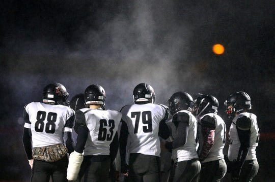 Steam rises as Letcworth/Warsaw huddles during the Far West Regional game against Cleveland Hill.