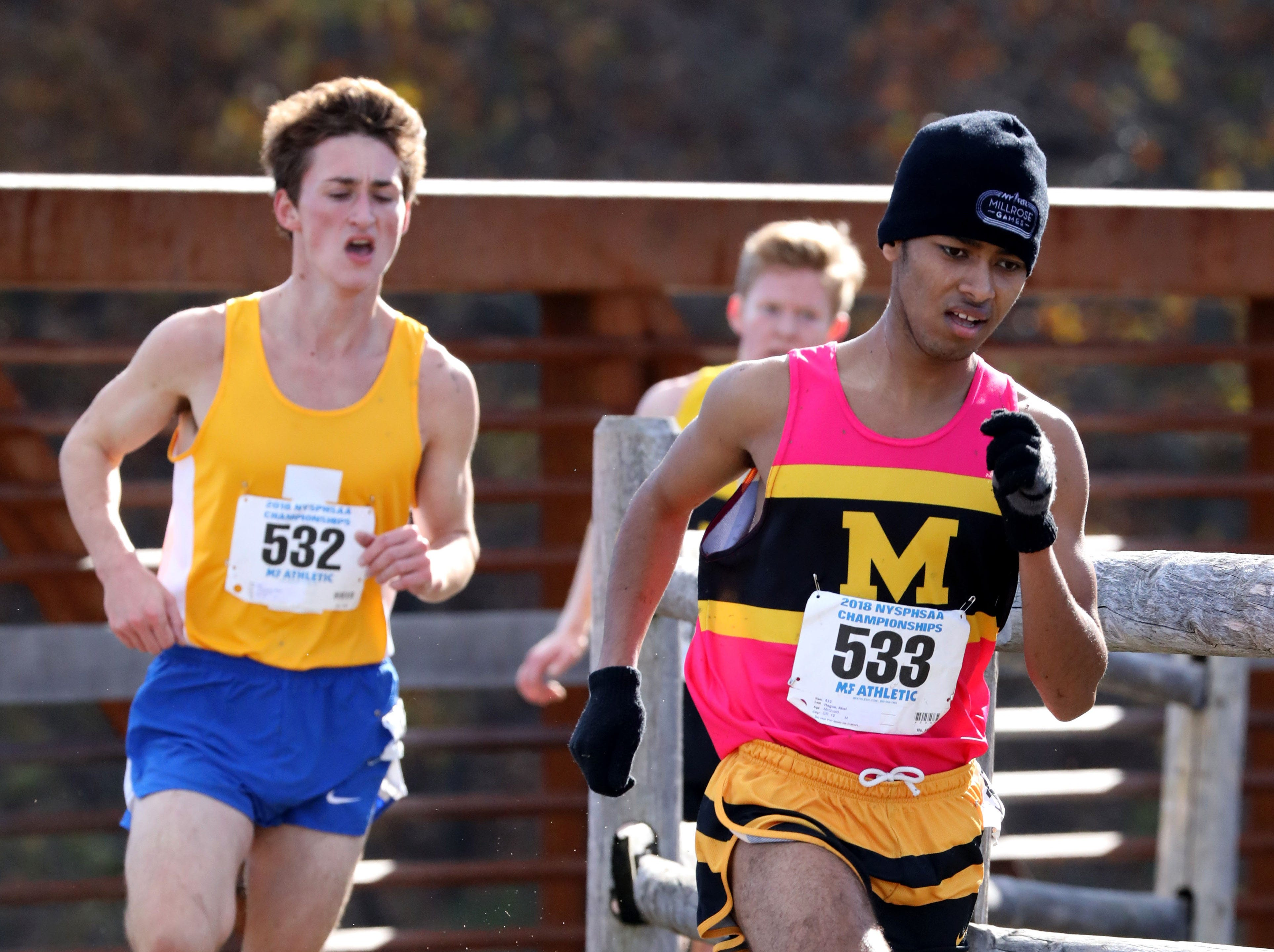Abel Hagos from McQuaid, right, followed by Ryan Thompson from Irondequoit, runs the boys Class A race during the 2018 NYSPHSAA Cross Country Championships at Sunken Meadow State Park in Kings Park on Nov. 10, 2018.