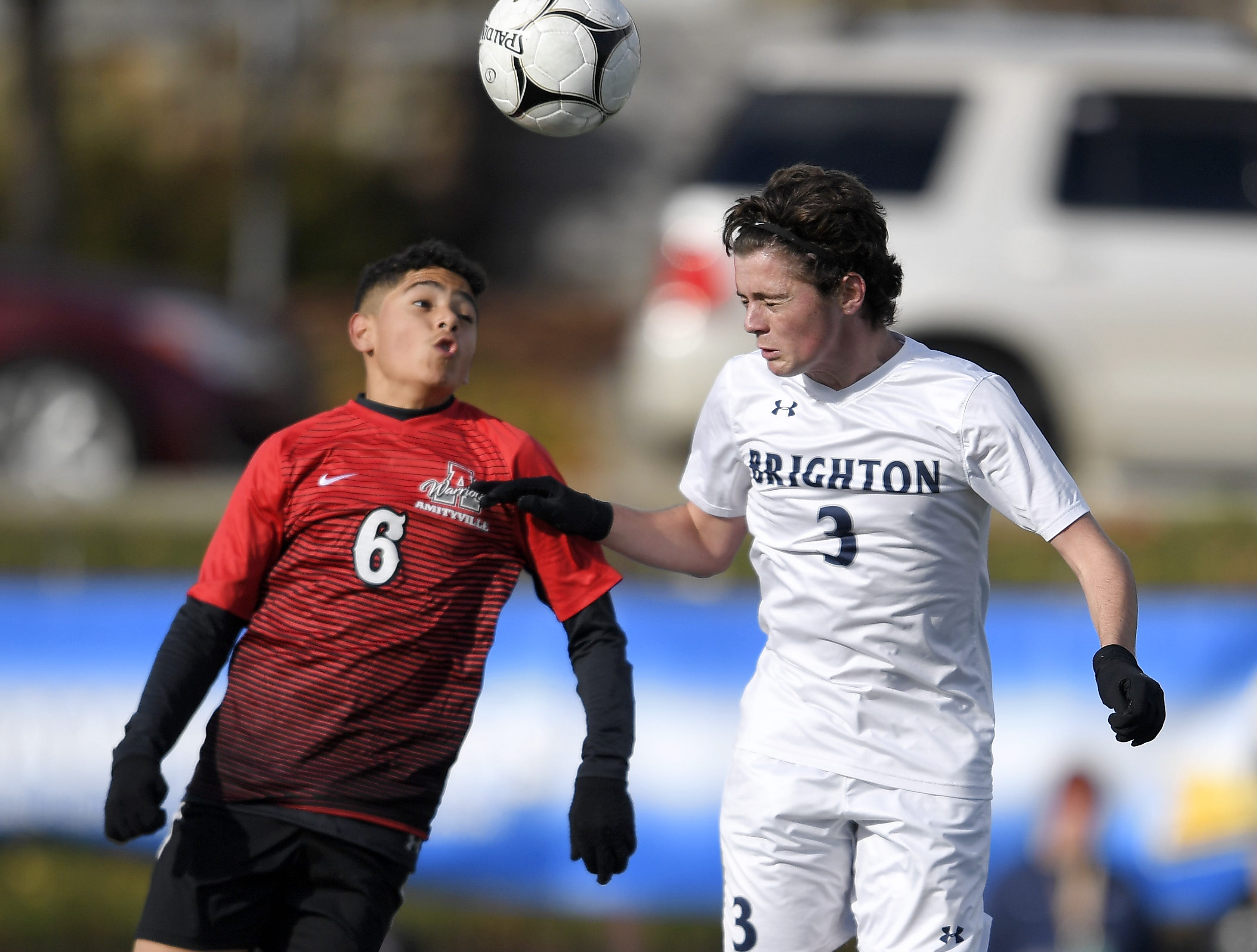 Brighton's Mat Ochs, right, jumps for a header against Amityville's Jeremy Guardado during a Class A semifinal at the NYSPHSAA Boys Soccer Championships in Newburgh, N.Y., Saturday, Nov. 10, 2018.