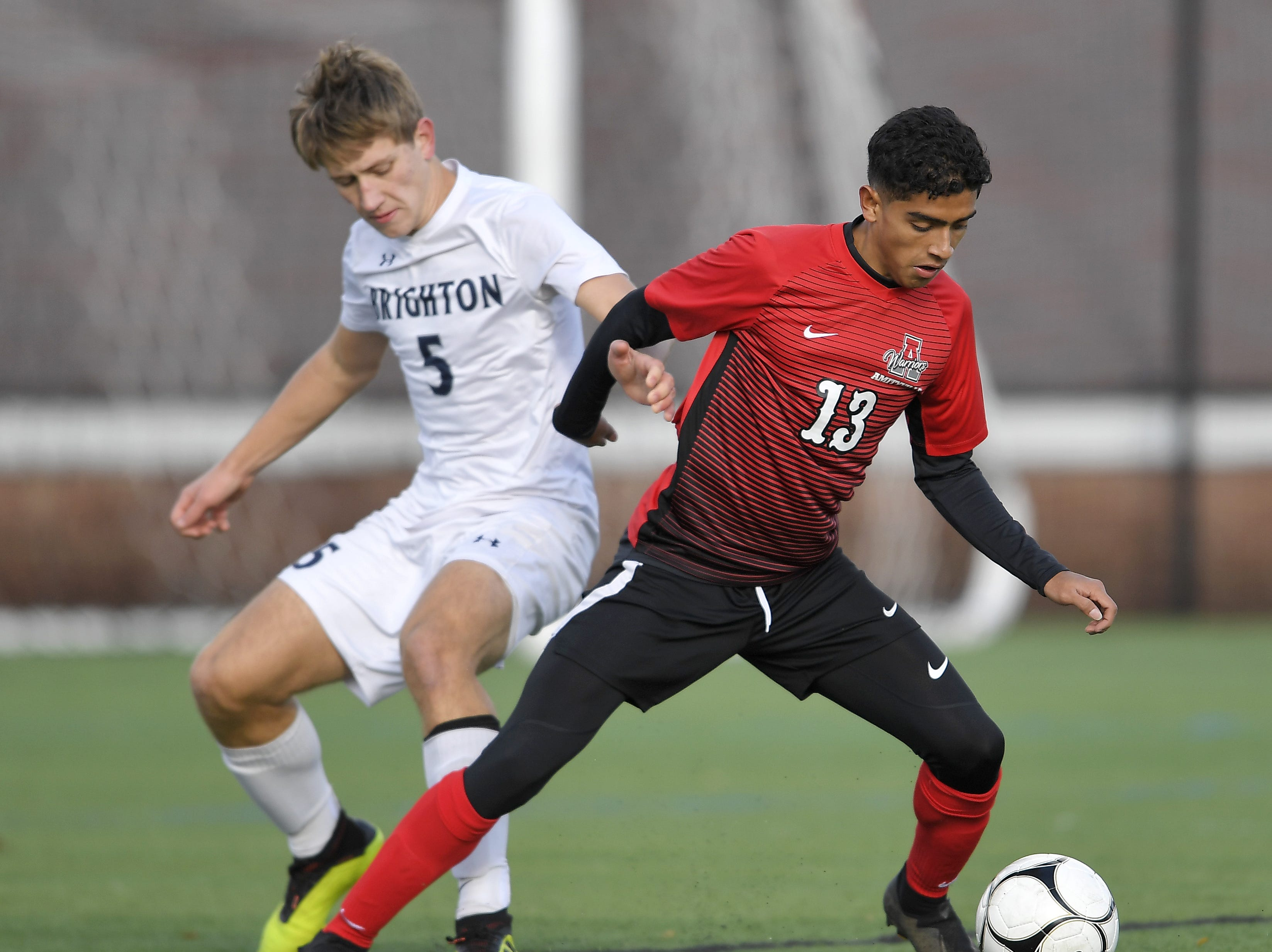 Brighton's Theo Viggiani-Cole, left, defends against Amityville's Rolman Guardado during a Class A semifinal at the NYSPHSAA Boys Soccer Championships in Newburgh, N.Y., Saturday, Nov. 10, 2018.