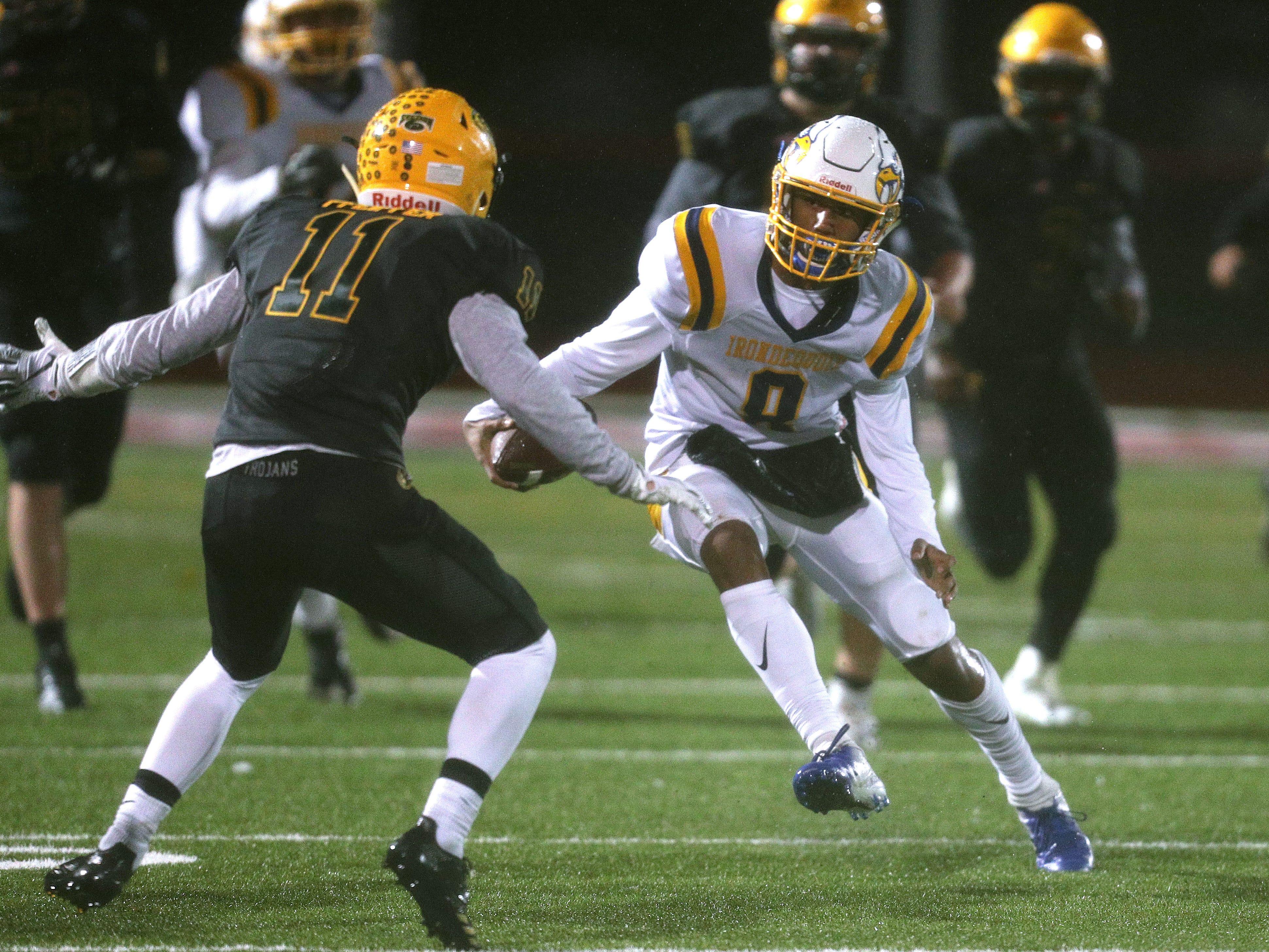 Irondequoit quarterback Freddy June Jr. slips past West Seneca East's Jesse Pfeiffer.
