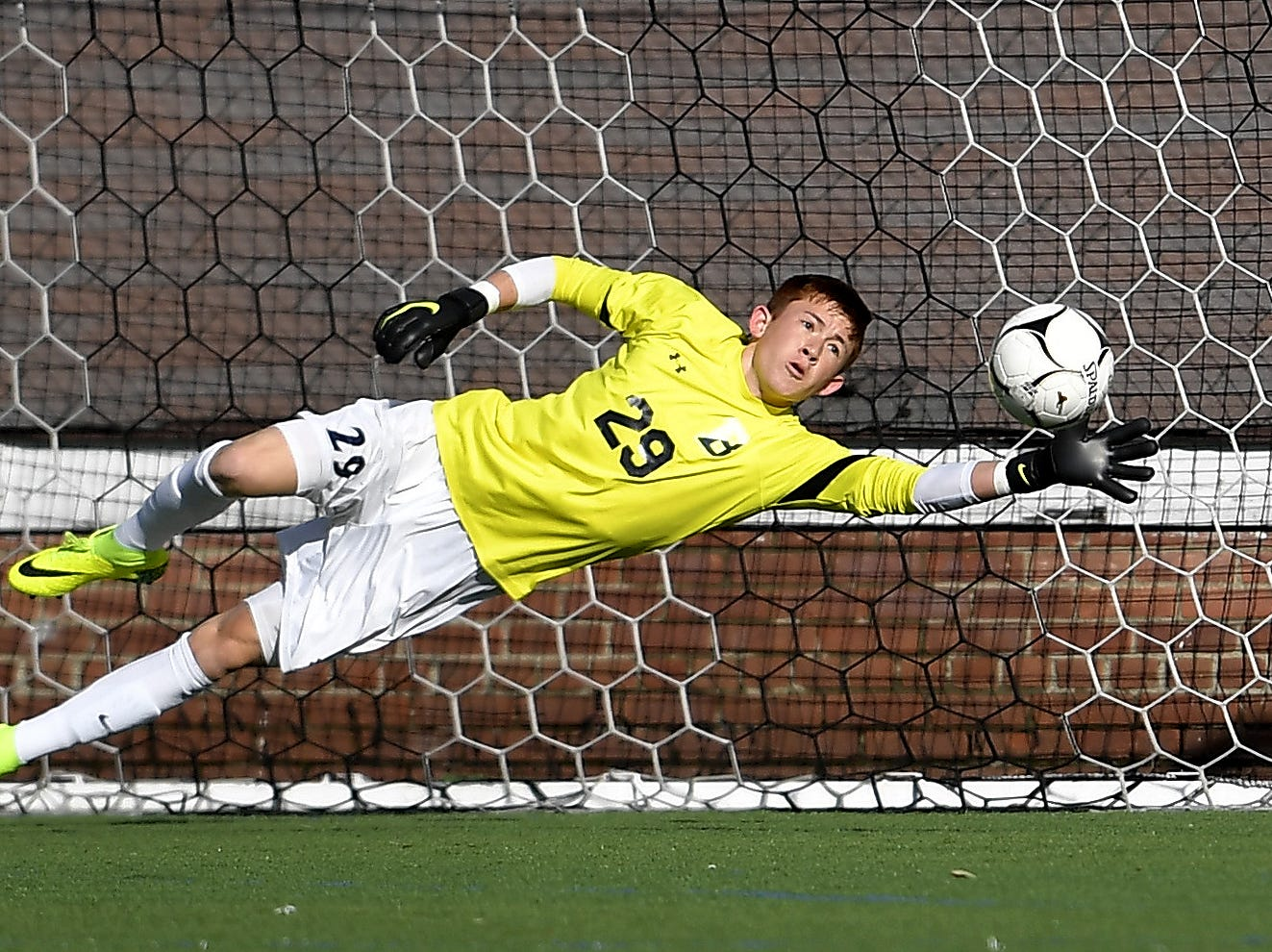 Brighton goalie Christian Burkhart dives for a ball but can't stop the shot for Amityville's first goal during a Class A semifinal at the NYSPHSAA Boys Soccer Championships in Newburgh, N.Y., Saturday, Nov. 10, 2018.