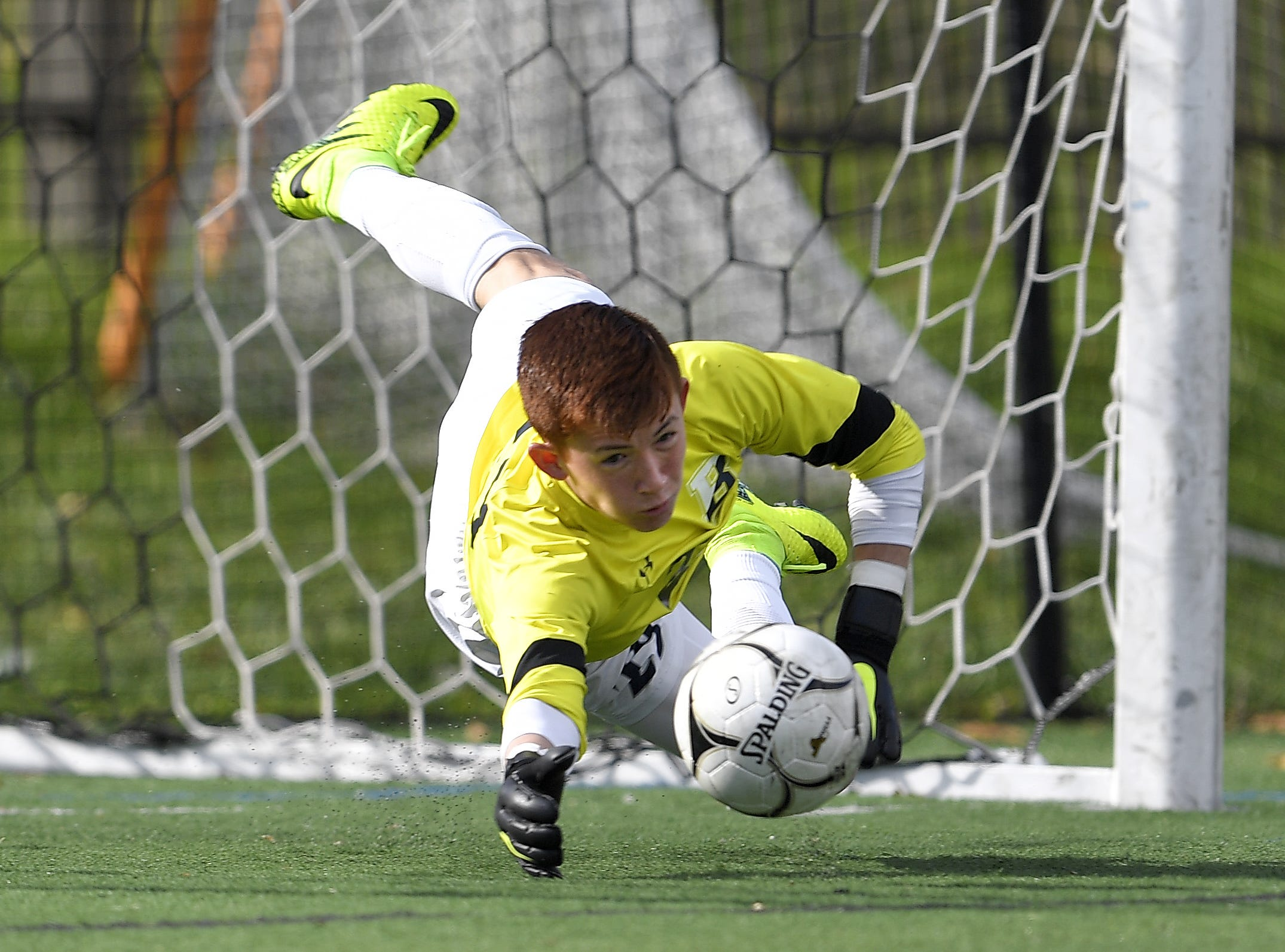 Brighton goalie Christian Burkhart makes a diving save during a Class A semifinal at the NYSPHSAA Boys Soccer Championships in Newburgh, N.Y., Saturday, Nov. 10, 2018.