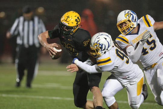 West Seneca East quarterback Shaun Dolac breaks free of this attempted sack by Irondequoit's Cameron Martin.