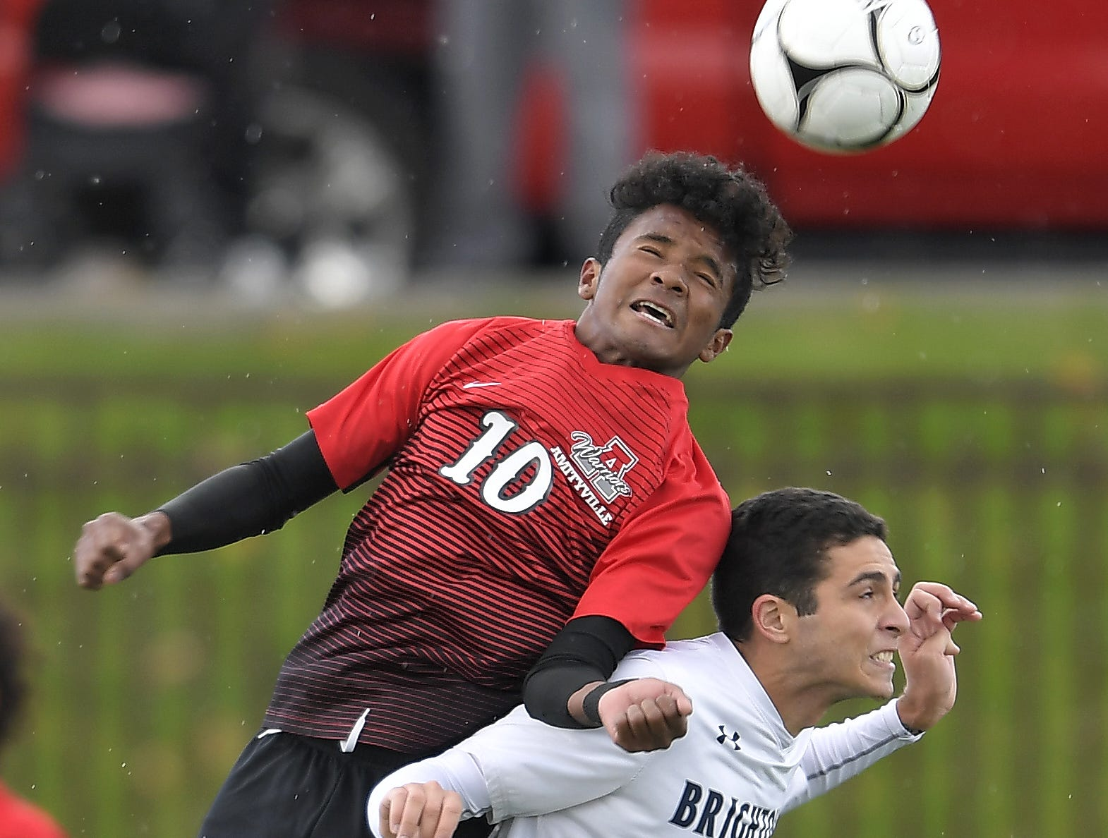 Amityville's Henry Martinez, left, jumps for a header over Brighton's Caio De Medeiros during a Class A semifinal at the NYSPHSAA Boys Soccer Championships in Newburgh, N.Y., Saturday, Nov. 10, 2018.