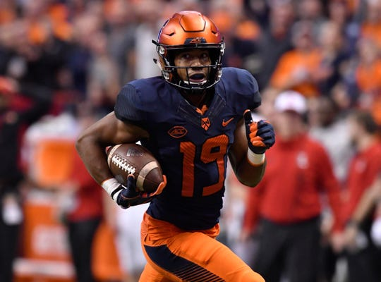 Syracusedefensive back Andre Cisco (19) carries the ball against the Louisville Cardinals during the second quarter of a game last season.