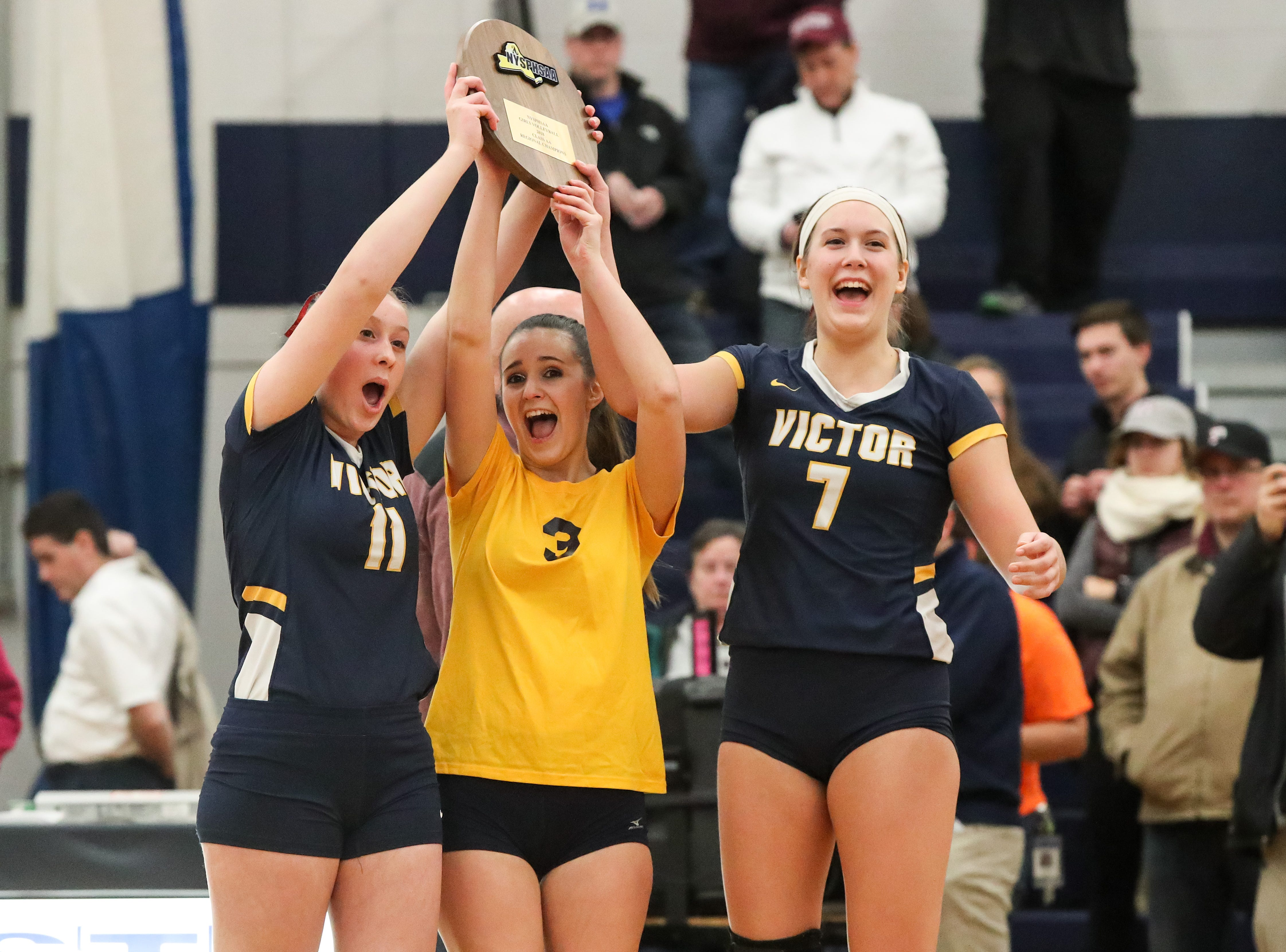 Victor captains Kate Simplicio (11), Ally McFadden (3), and Makenzie Bills (7) hold up their trophy after defeating Orchard Park in the Class AA West Regional high school girls volleyball match at Webster Thomas on Nov. 9, 2018.