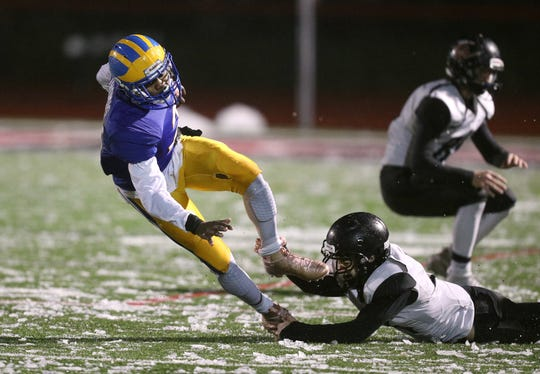 Cleveland Hill quarterback Javon Thomas is tripped up by Letchworth/Warsaw's Dalton English.
