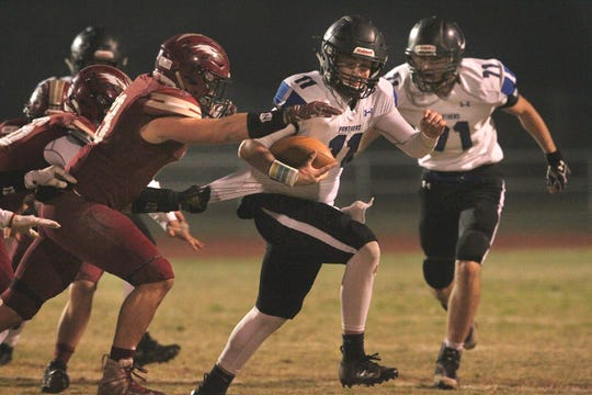 U-Prep quarterback Dylan Cabral (11) tries to break away from West Valley defenders Friday. West Valley won the game 55-6.