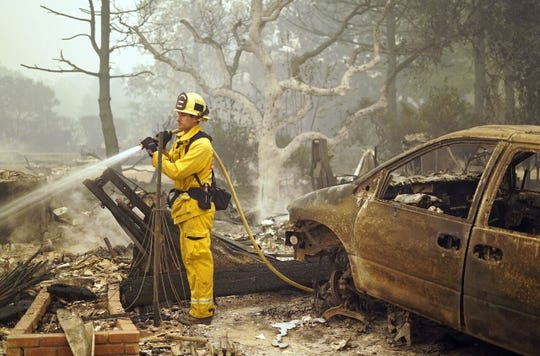 A firefighter pumps water on the smoldering remains of a residence in Paradise, California on Friday, Nov. 9, 2018.