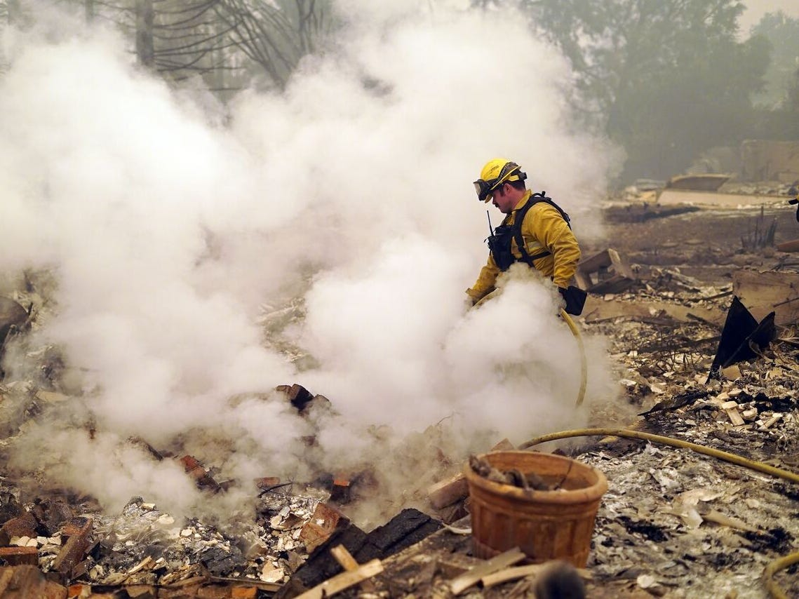 A firefighter pumps water on the smoldering remains of a residence on Friday, Nov. 9, 2018. The Camp Fire devastated Paradise, California on Thursday, Nov. 8, 2018