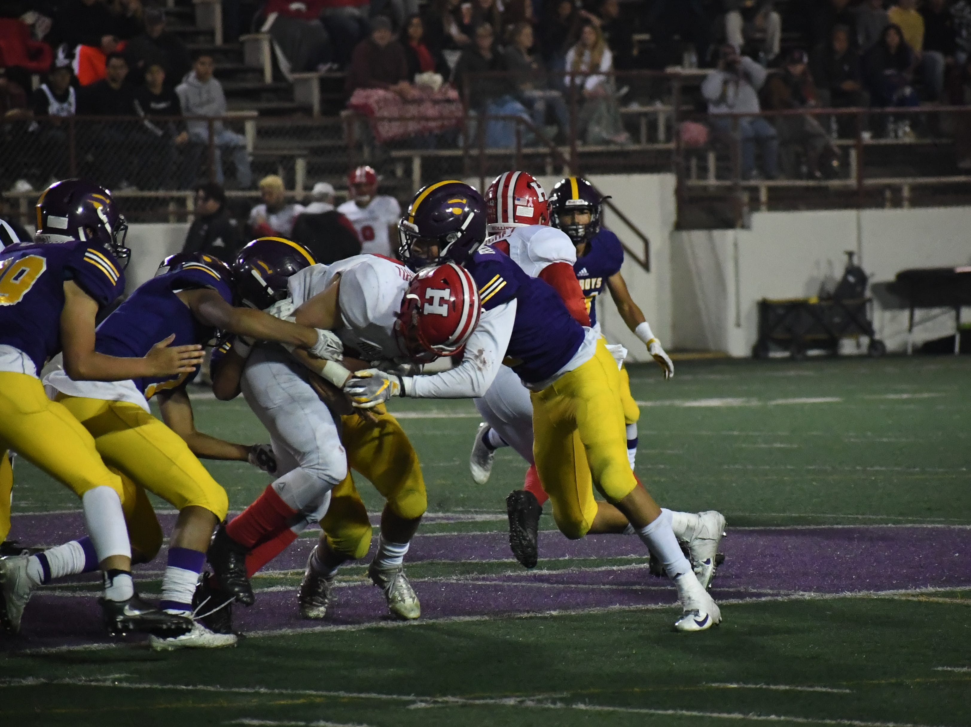 Linebackers Nick Marquez, Joey Moag and safety Zachary Robison (2) wrap up a San Benito running back.