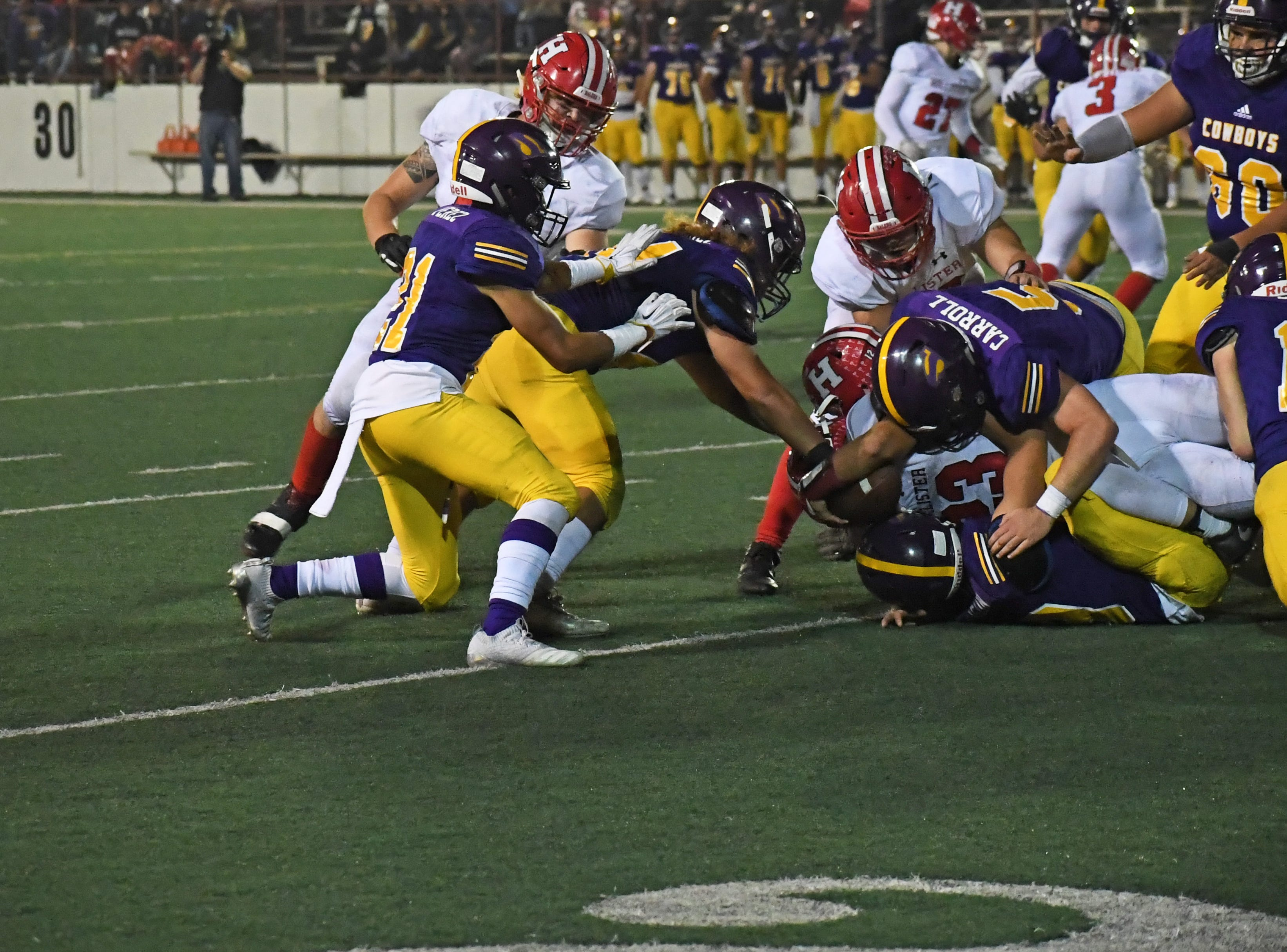 Linebacker Tyler Carroll (5) and safety Cade Smith (19) take down a San Benito running back.