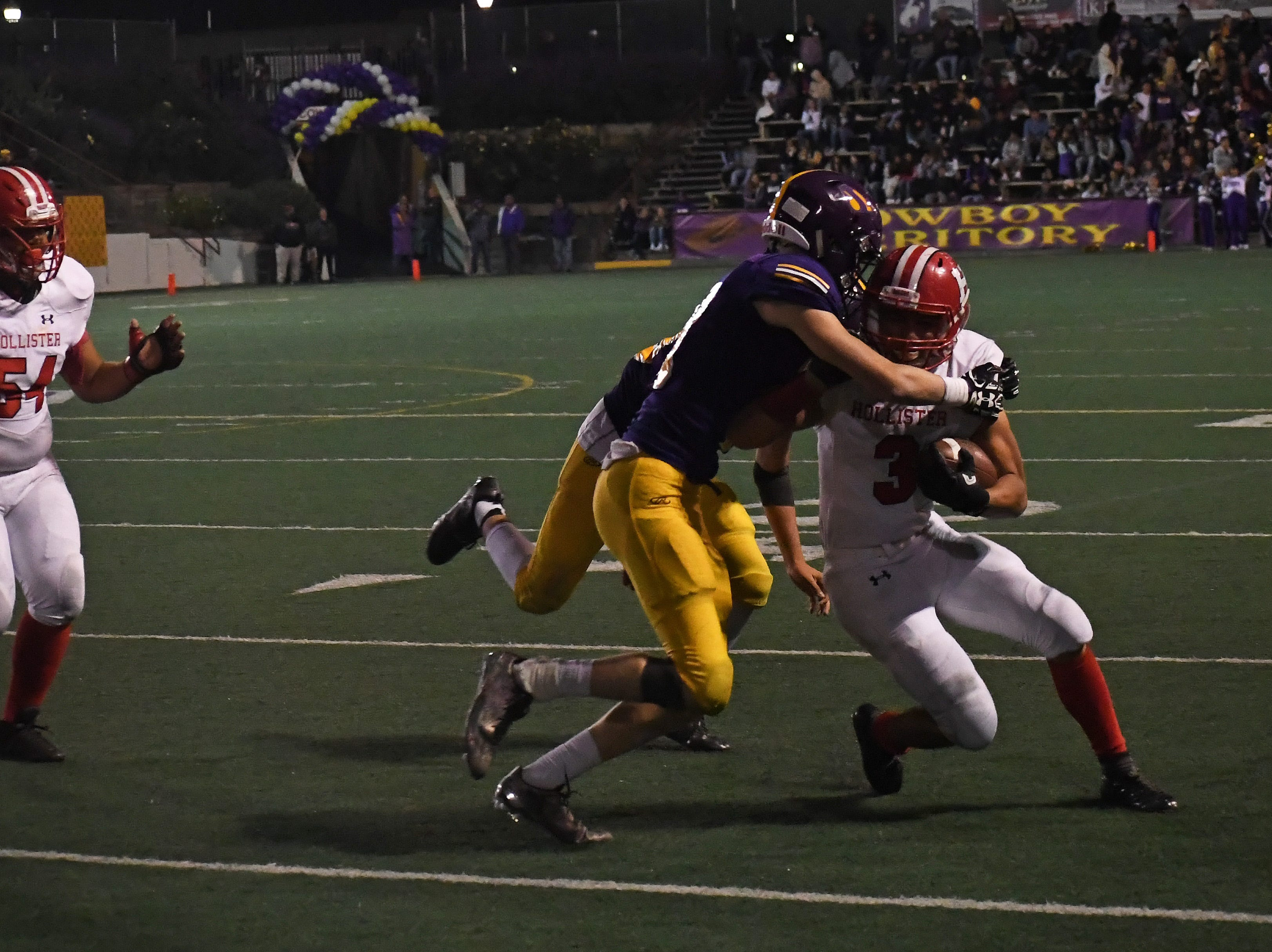 Safety Zachary Robison (2) and another defender take down a San Benito running back.