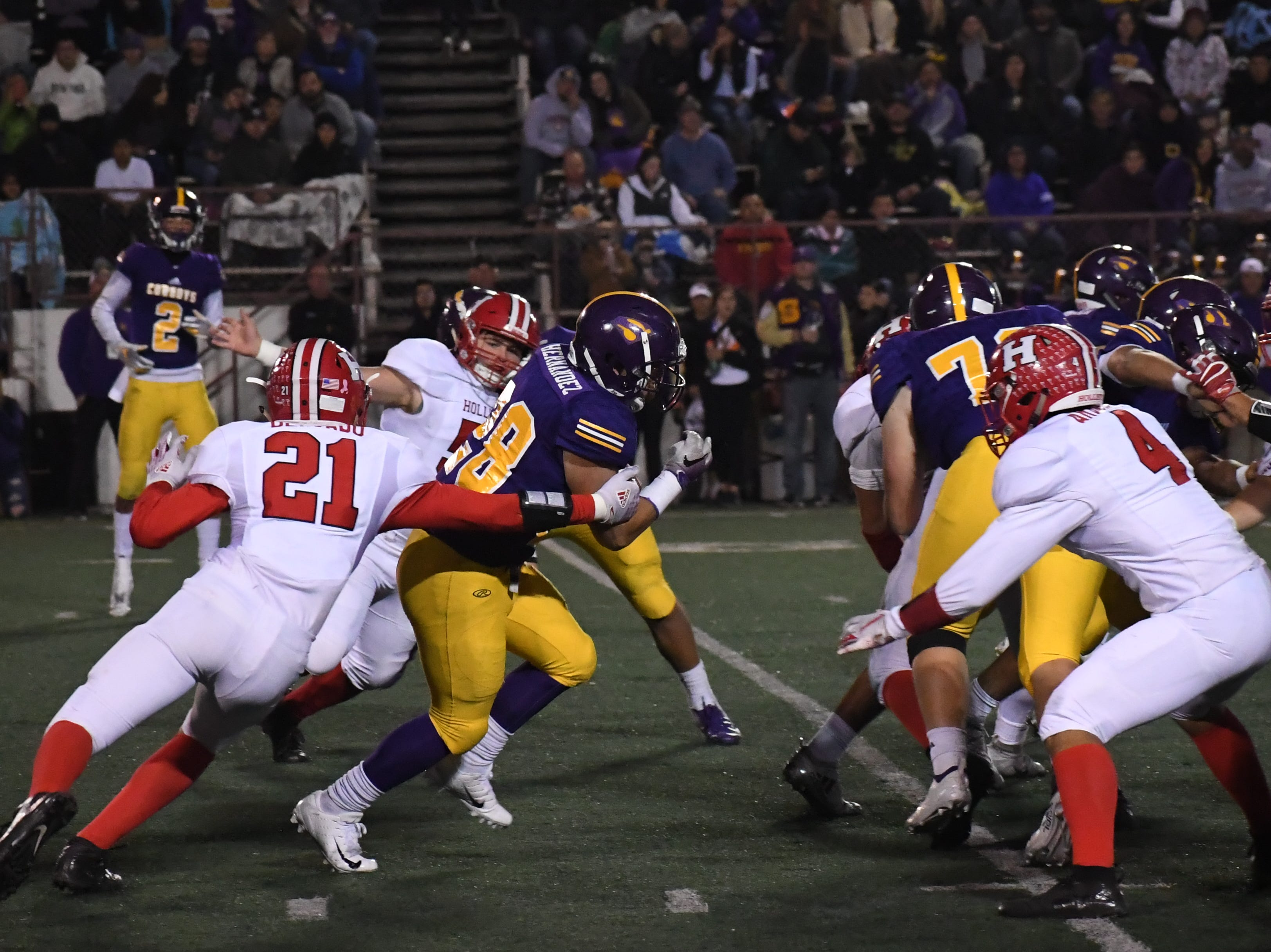 Running back Abraham Hernandez (28)  evades an arm tackle while running through the hole.