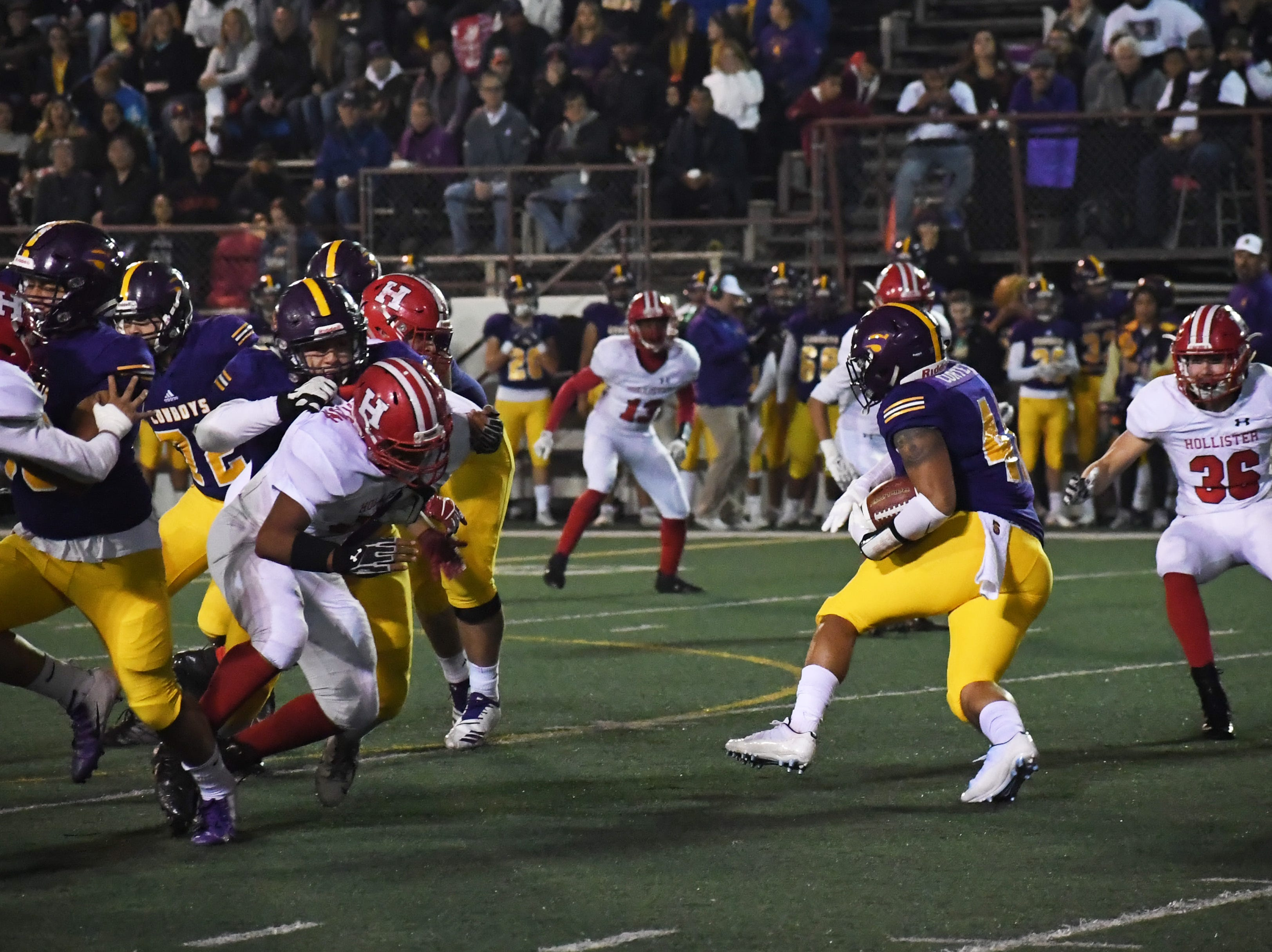 Running back Mike Cortez (41) cuts right to avoid a tackler.
