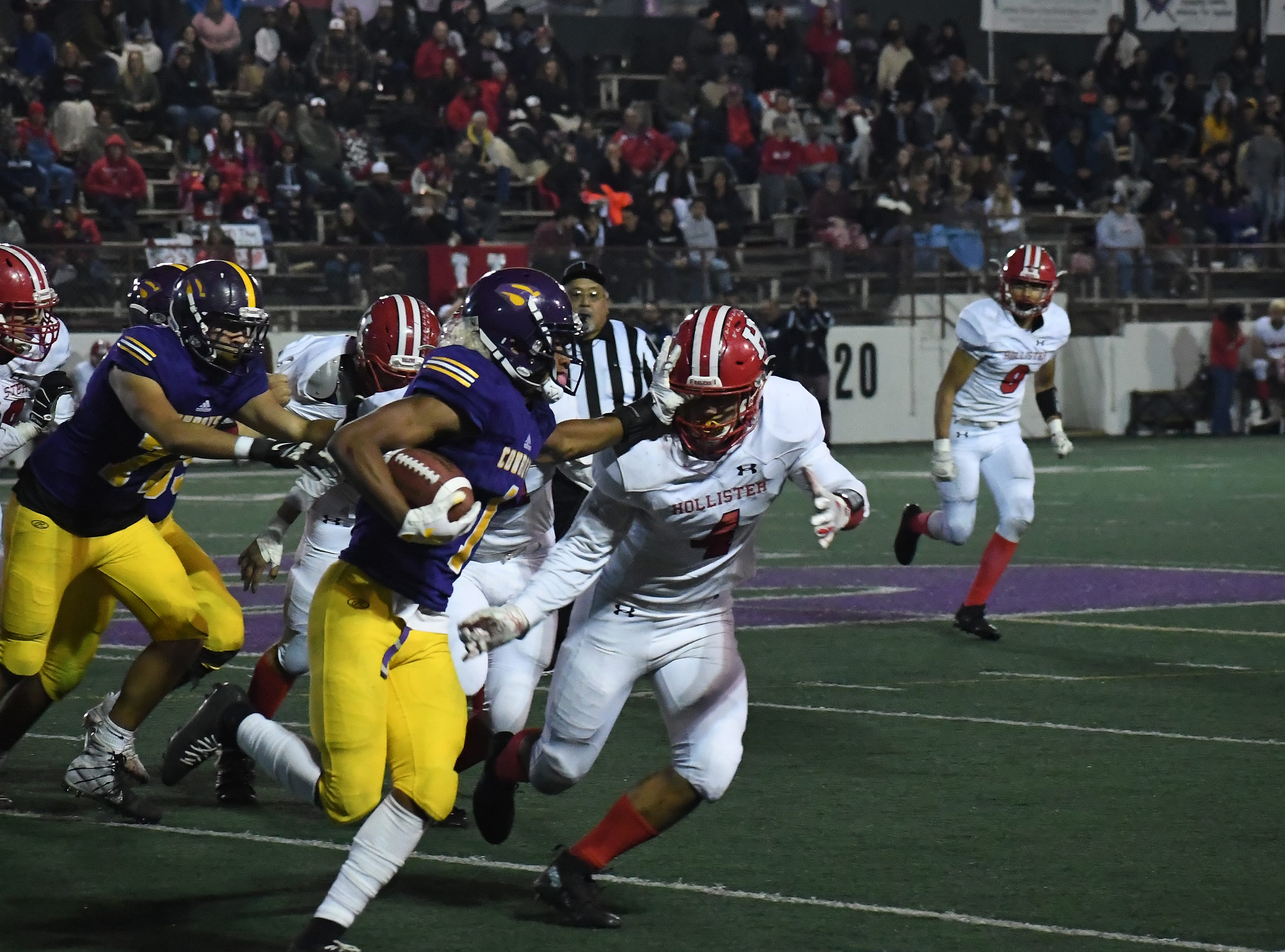 Wide receiver Poe Gaskins (1) stiff arms a would-be tackler.