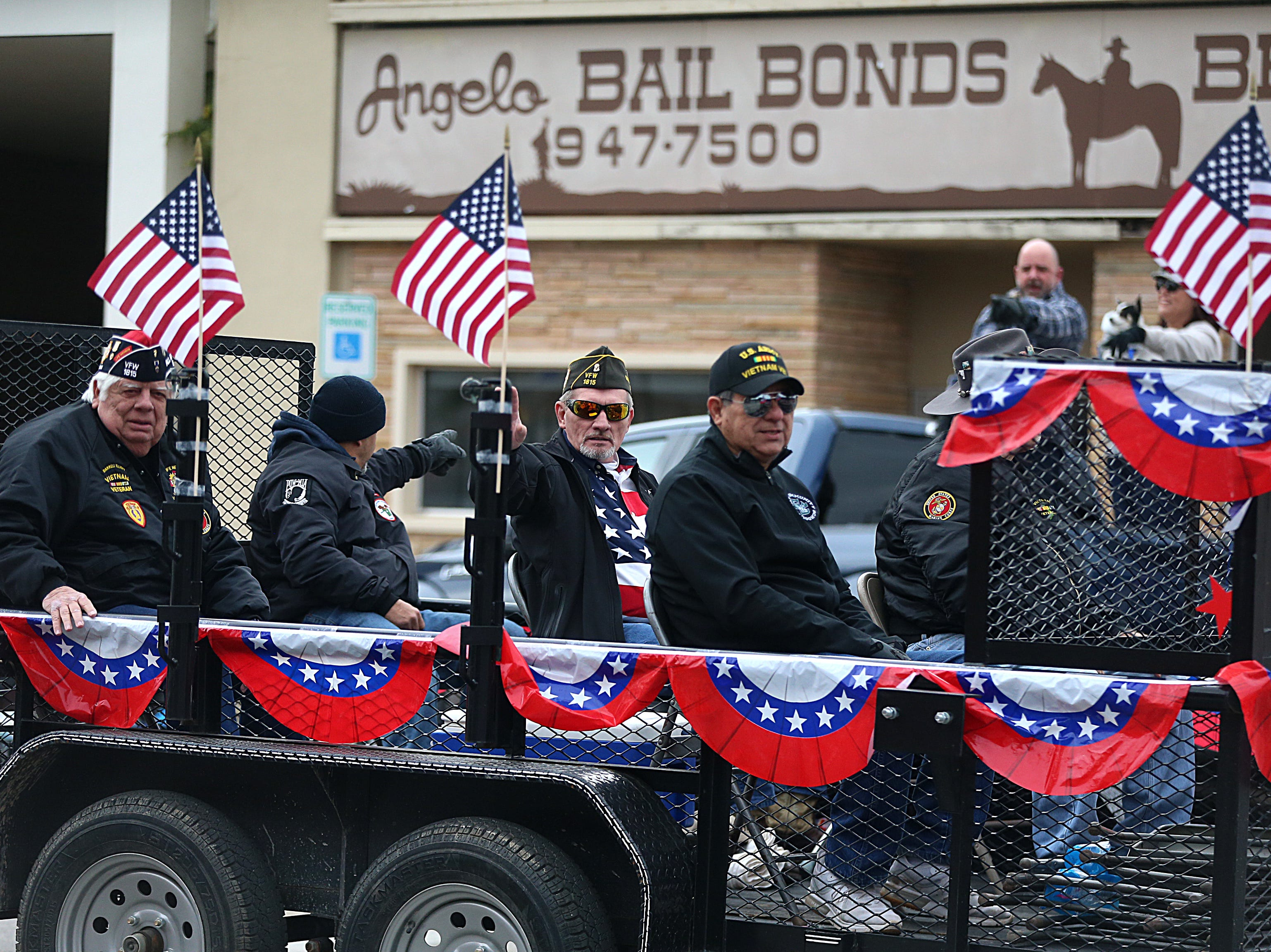 "Veterans ride on a float and wave to spectators Saturday, Nov. 10, 2018, during the 15th annual Veterans Day Parade, themed ""Honoring faithful freedom defenders."""