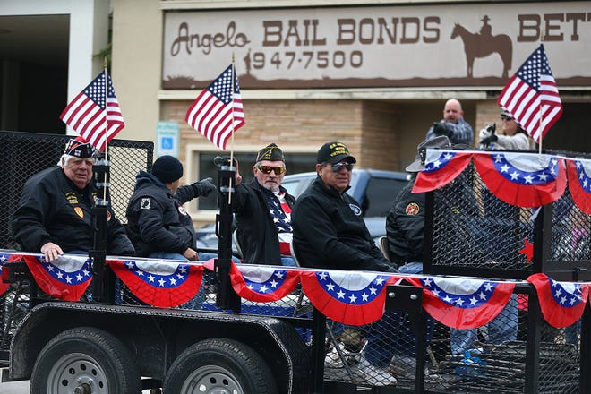 """Veterans ride on a float and wave to spectators Saturday, Nov. 10, 2018, during the 15th annual Veterans Day Parade, themed """"Honoring faithful freedom defenders."""""""
