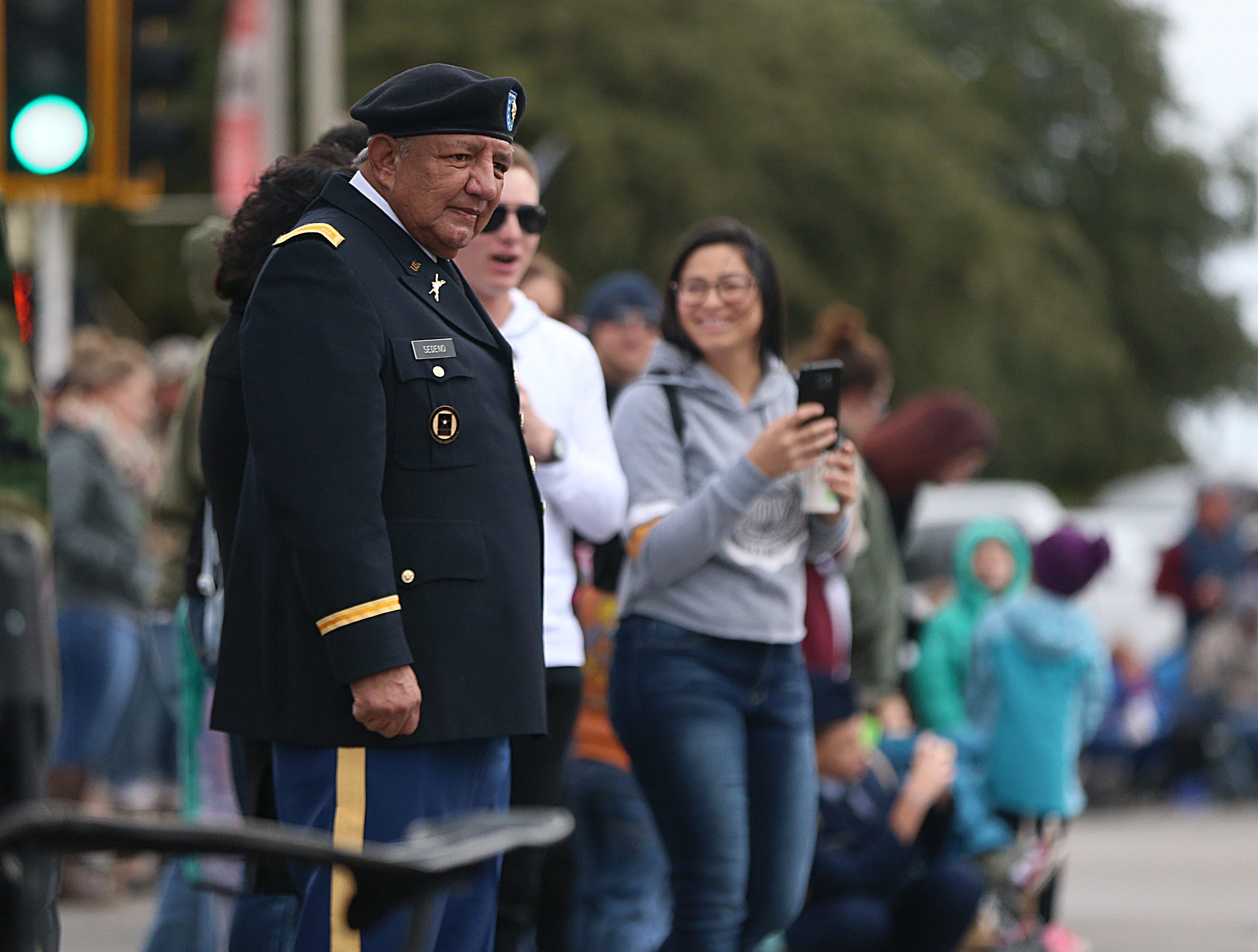 "Retired U.S. Army veteran Domingo Sedeno watches at floats ease by Saturday, Nov. 10, 2018, during the 15th annual Veterans Day Parade, themed ""Honoring faithful freedom defenders."""