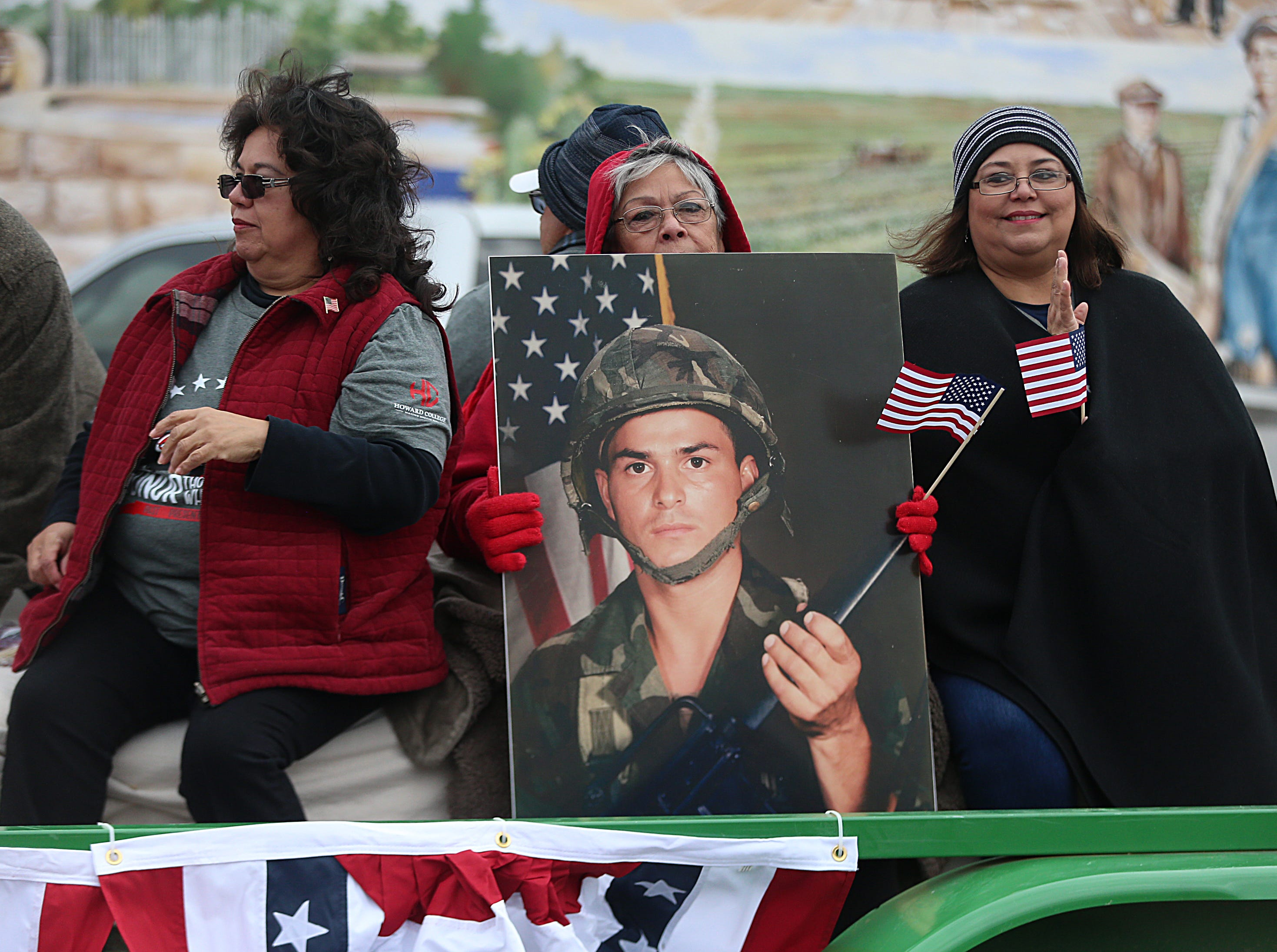 "Women holding a photo of a solider ride on the Howard College float Saturday, Nov. 10, 2018, during the 15th annual Veterans Day Parade, themed ""Honoring faithful freedom defenders."""