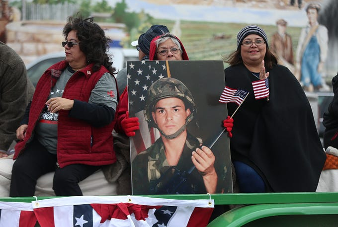"""Women holding a photo of a solider ride on the Howard College float Saturday, Nov. 10, 2018, during the 15th annual Veterans Day Parade, themed """"Honoring faithful freedom defenders."""""""
