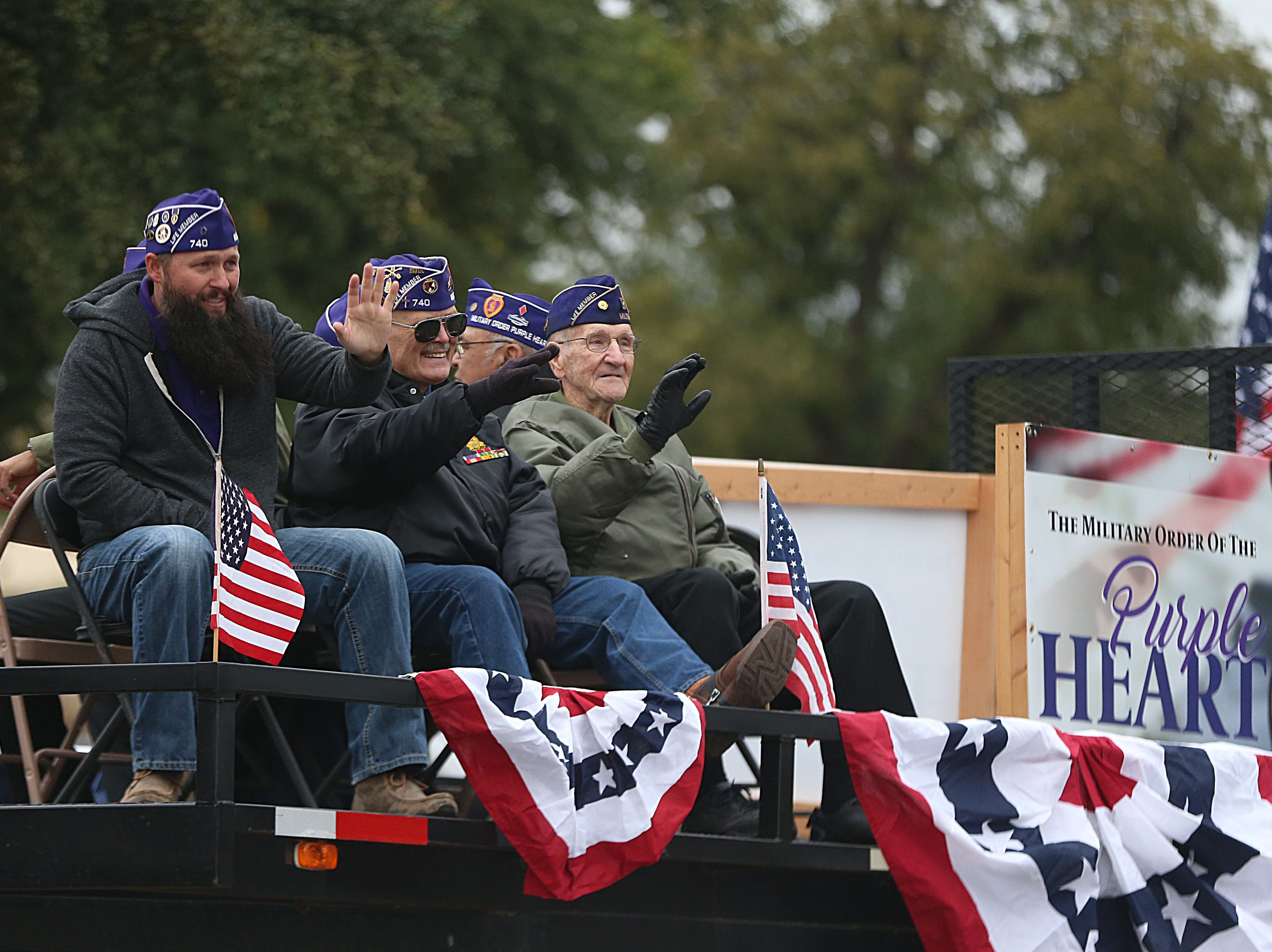 "Veterans riding in a float wave to spectators downtown Saturday, Nov. 10, 2018, during the 15th annual Veterans Day Parade, themed ""Honoring faithful freedom defenders."""