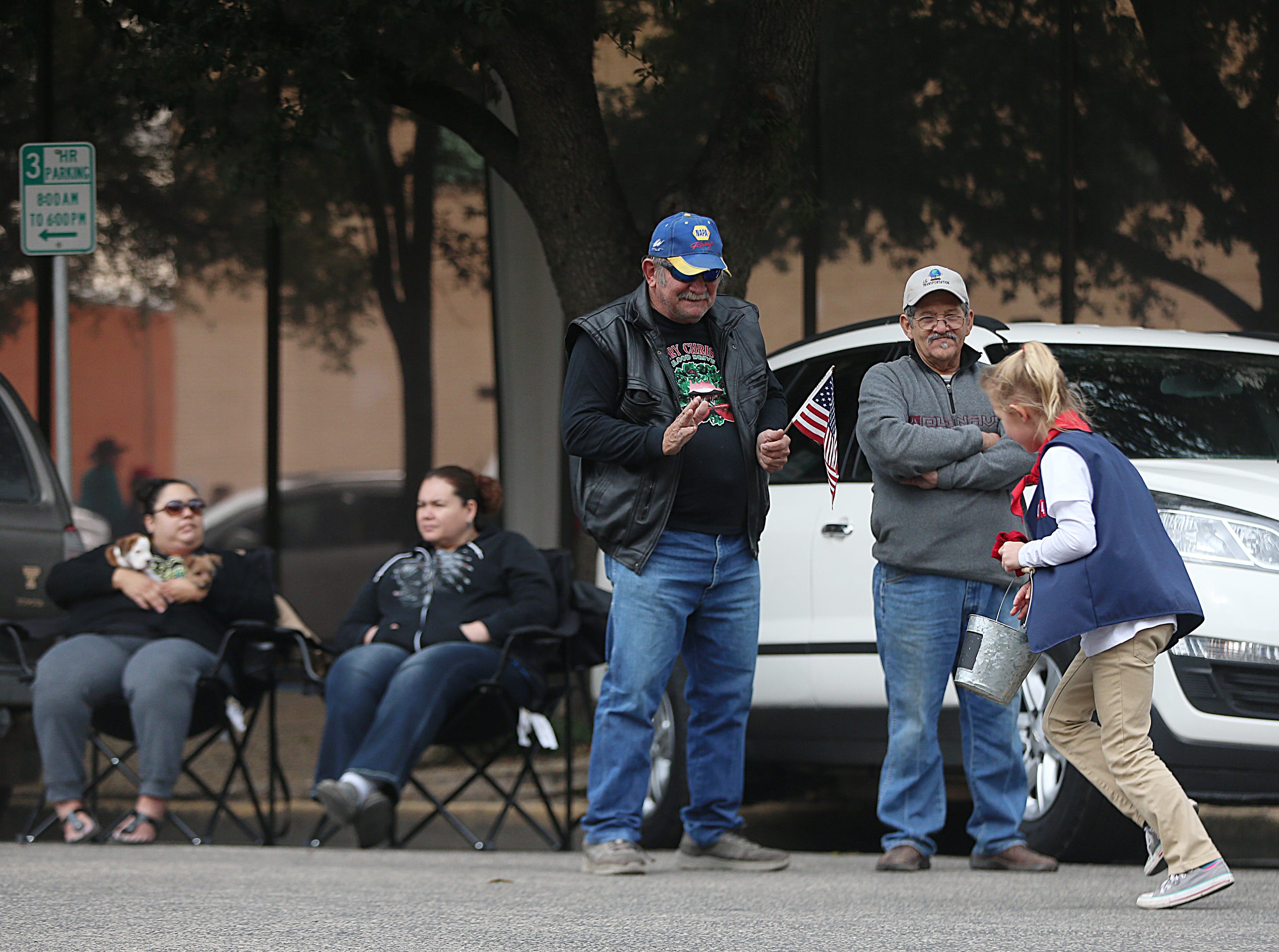 "Spectators wave at a little girl tossing out candy downtown Saturday, Nov. 10, 2018, during the 15th annual Veterans Day Parade, themed ""Honoring faithful freedom defenders."""