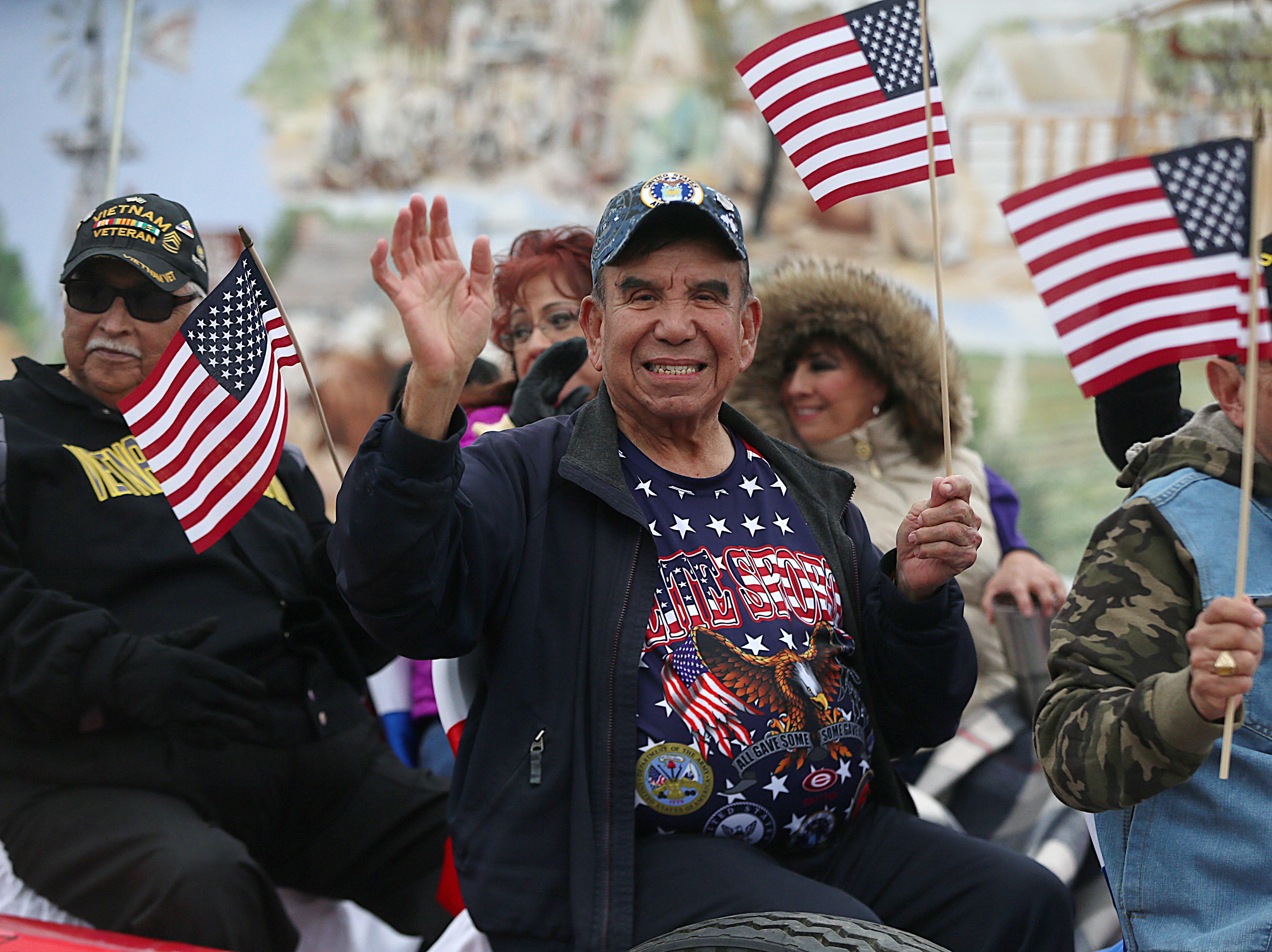 "Veterans carrying American flags wave to spectators Saturday, Nov. 10, 2018, during the 15th annual Veterans Day Parade, themed ""Honoring faithful freedom defenders."""