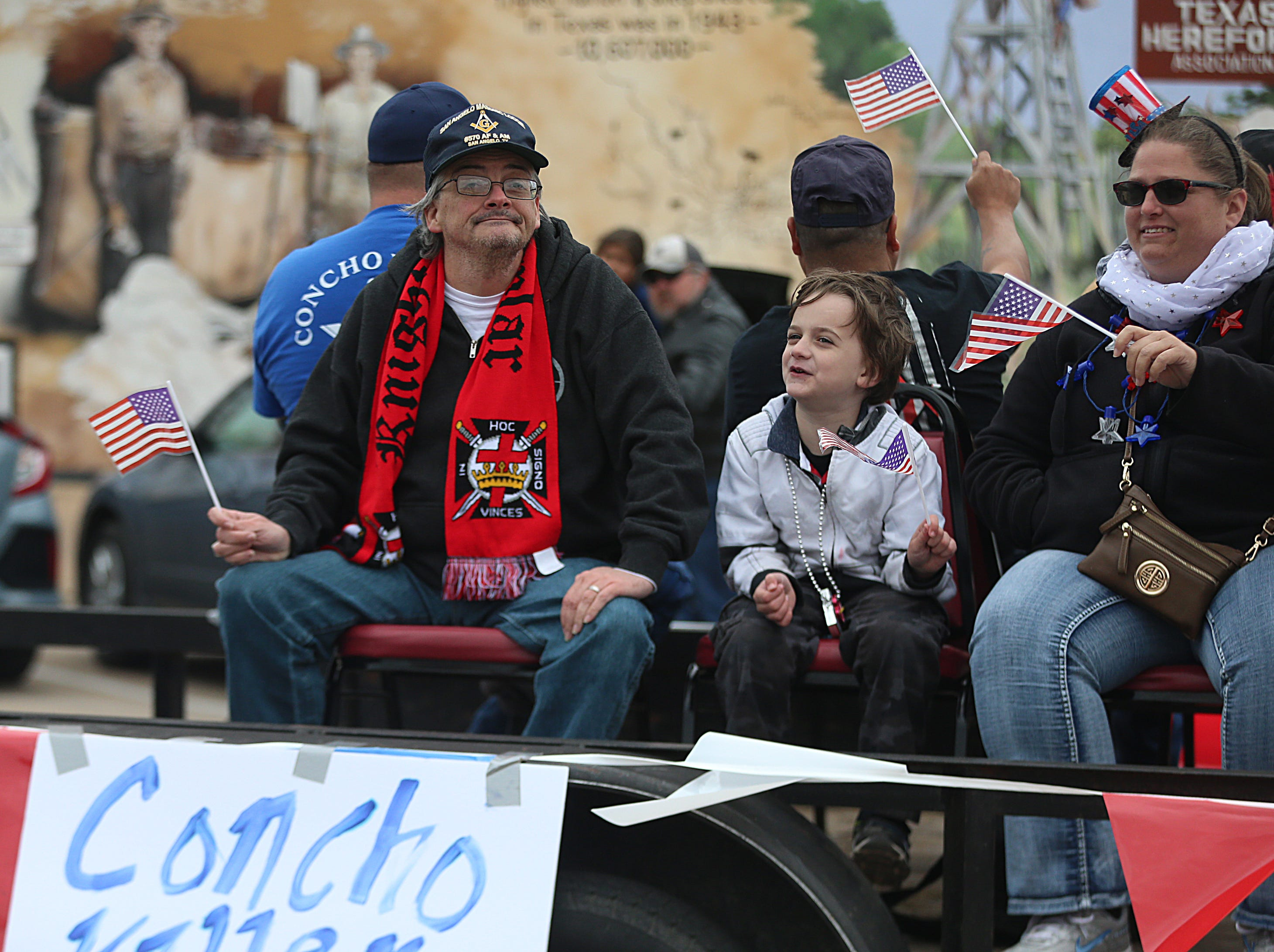 "Parade participants wave American flags on a float Saturday, Nov. 10, 2018, during the 15th annual Veterans Day Parade, themed ""Honoring faithful freedom defenders."""