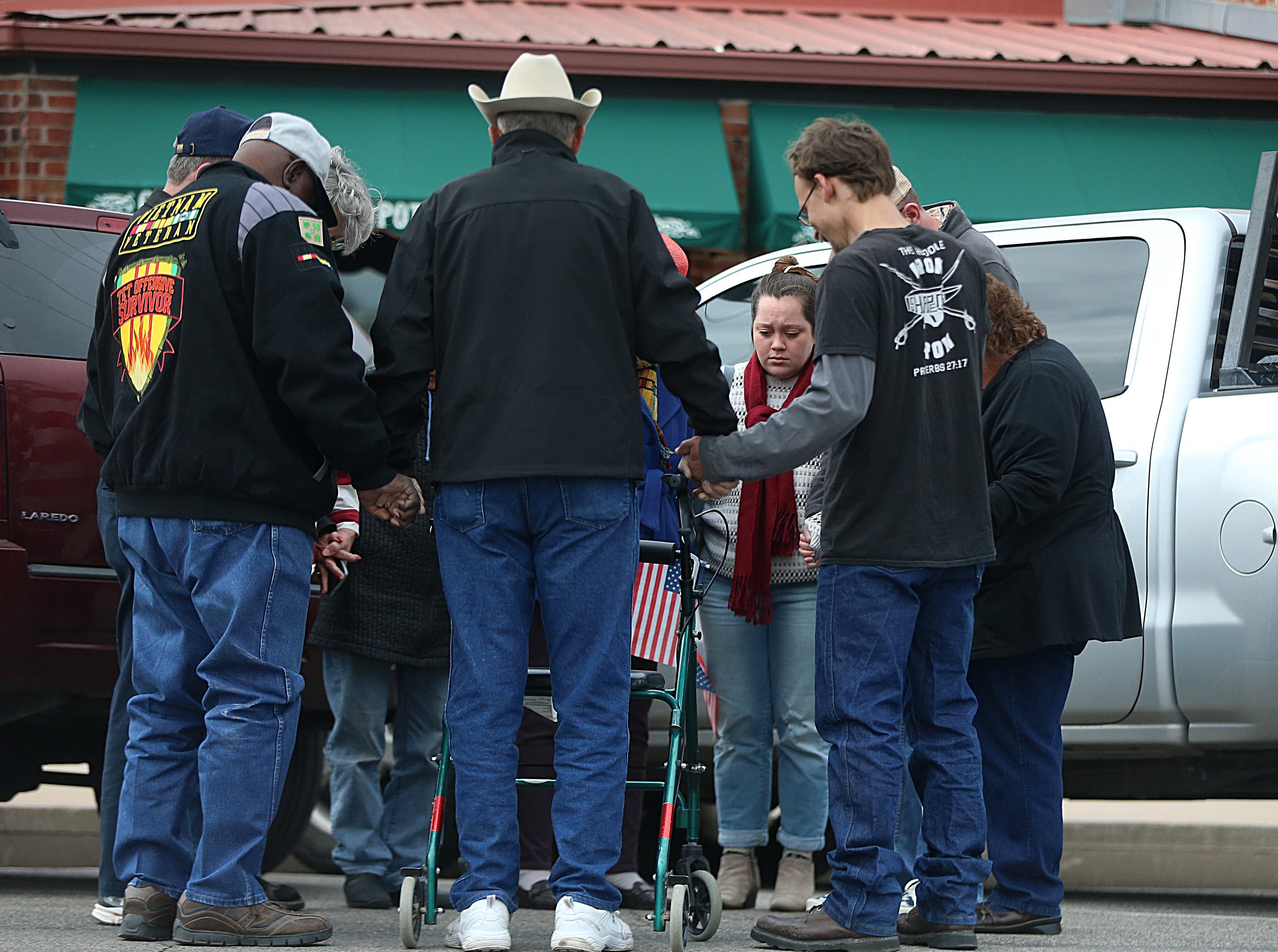 "People hold hands during a prayer chain Saturday, Nov. 10, 2018, during the 15th annual Veterans Day Parade, themed ""Honoring faithful freedom defenders."""