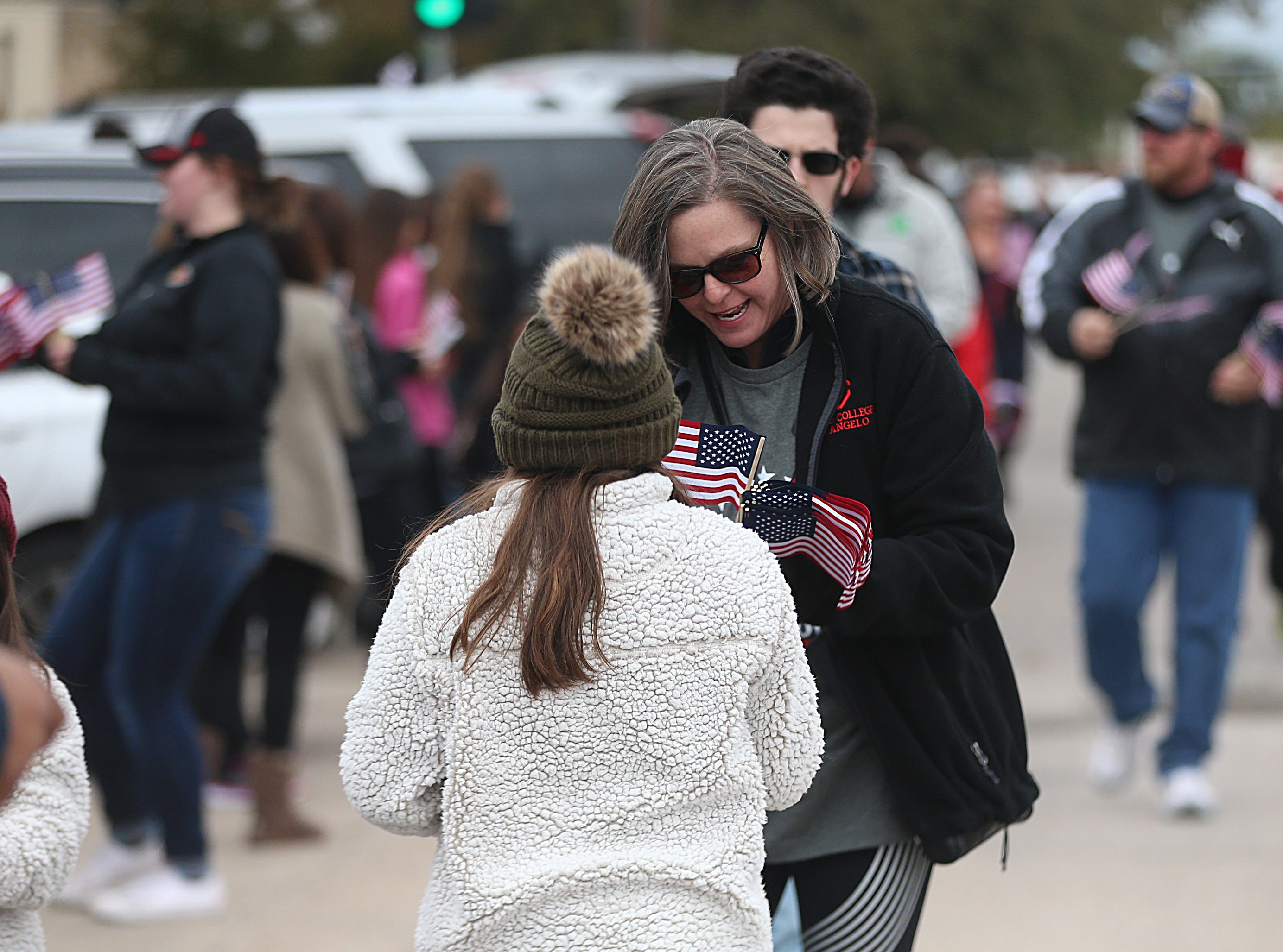 "A woman hands out American flags downtown Saturday, Nov. 10, 2018, during the 15th annual Veterans Day Parade, themed ""Honoring faithful freedom defenders."""