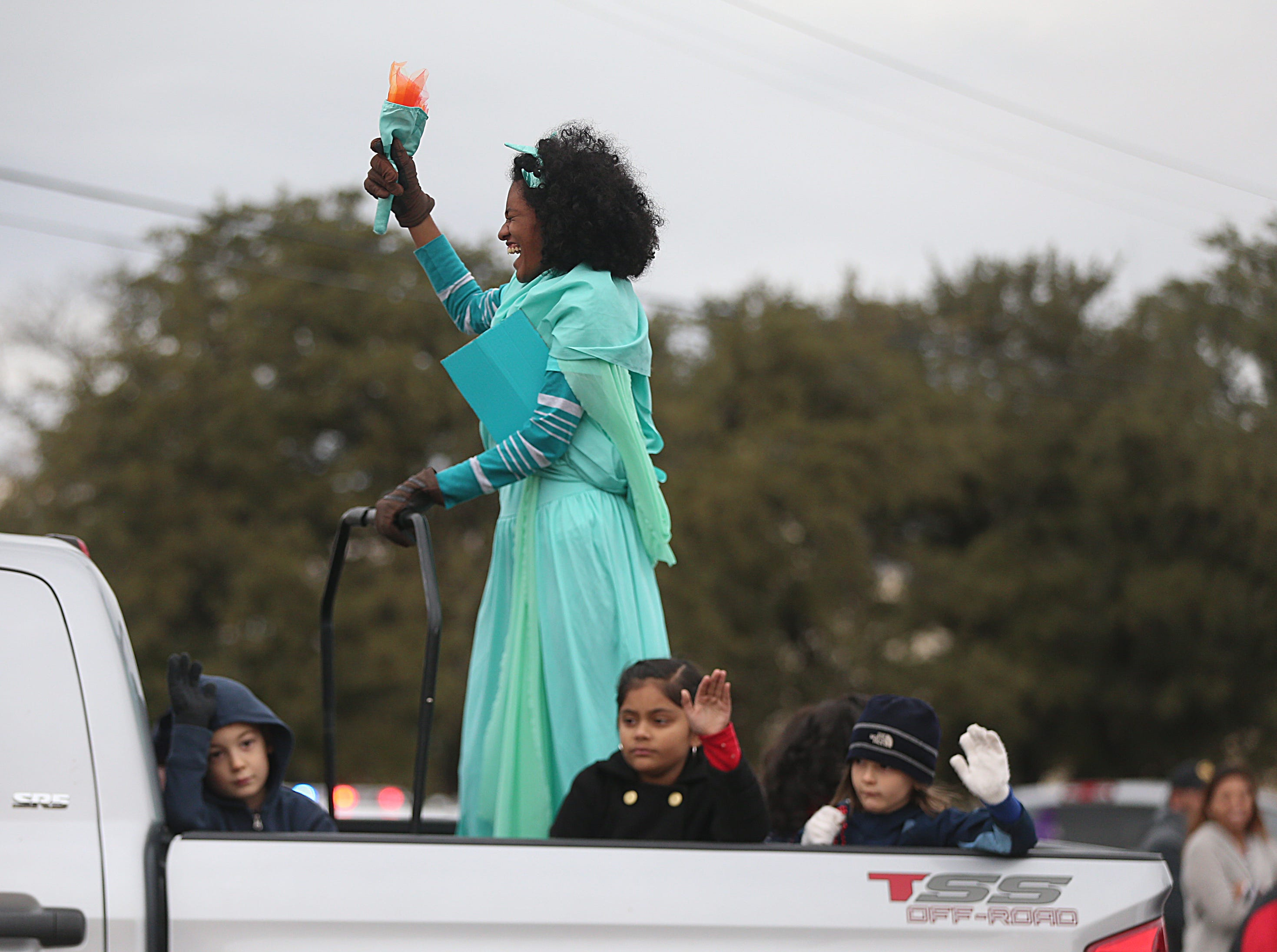 "A girl dressed as the Statue of Liberty rides in the back of a truck Saturday, Nov. 10, 2018, during the 15th annual Veterans Day Parade, themed ""Honoring faithful freedom defenders."""