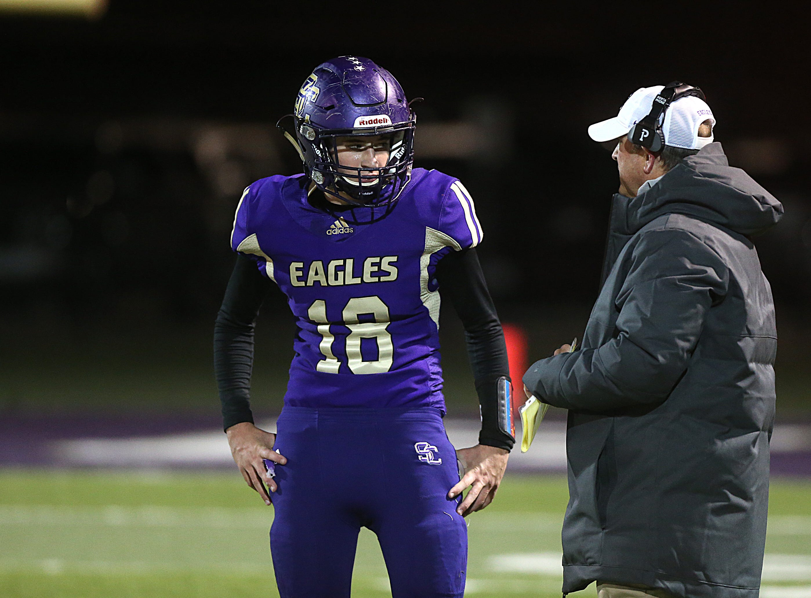 Sterling City's Hudson Cox (#18) talks with one of his coaches Friday, Nov. 9, 2018 during their game against Garden City.