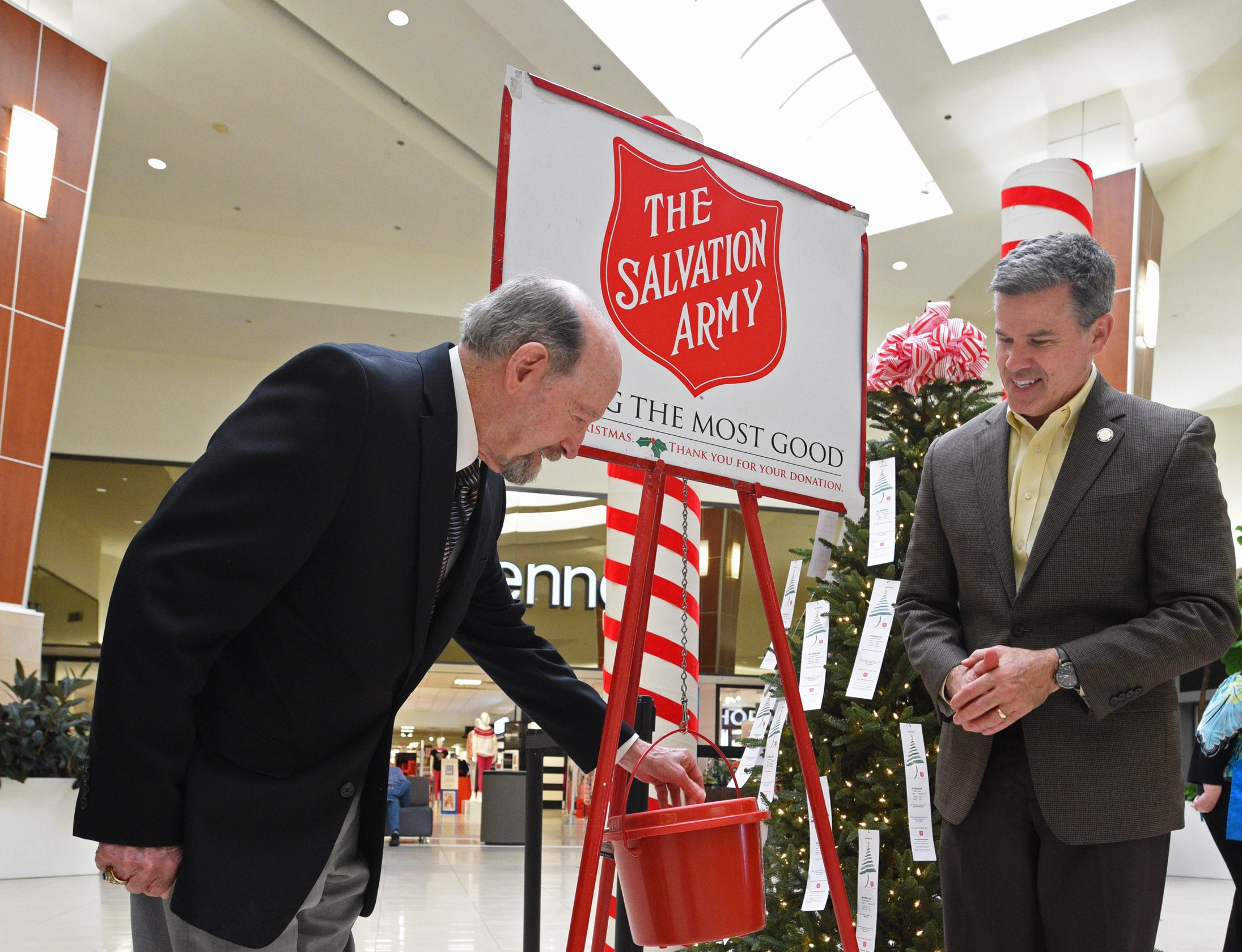 Bossier Mayor Lo Walker (left) and Brain Crawford put the first donations in the kettle at the Salvation Army Angel Tree and Red Kettle Campaign 2018 Holiday Kick-off at Bossier City's Pierre Bossier Mall.